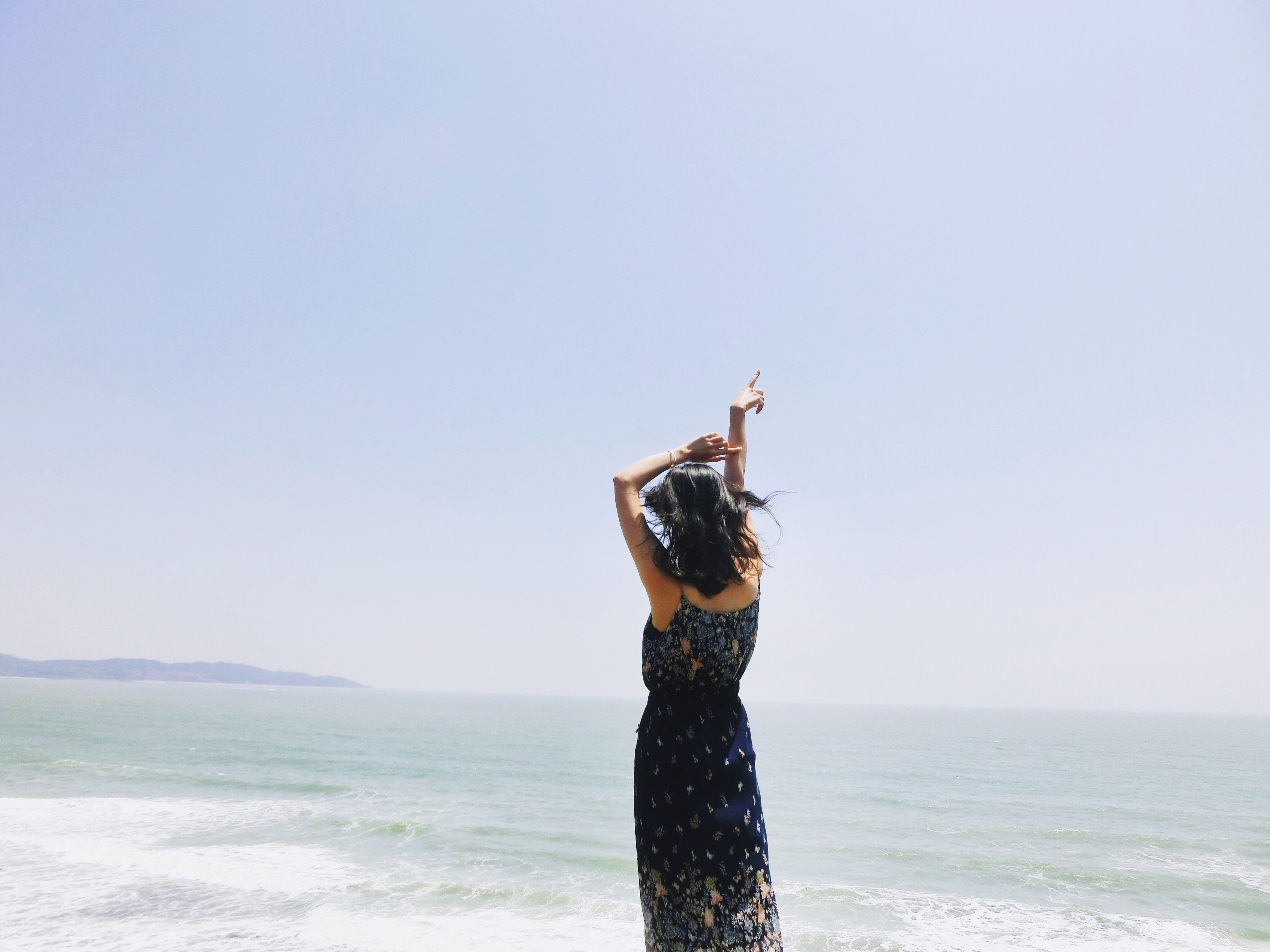 sea, horizon over water, clear sky, real people, one person, standing, arms raised, outdoors, beach, lifestyles, water, leisure activity, sky, nature, day, blue, beauty in nature, women, young adult, adult, people