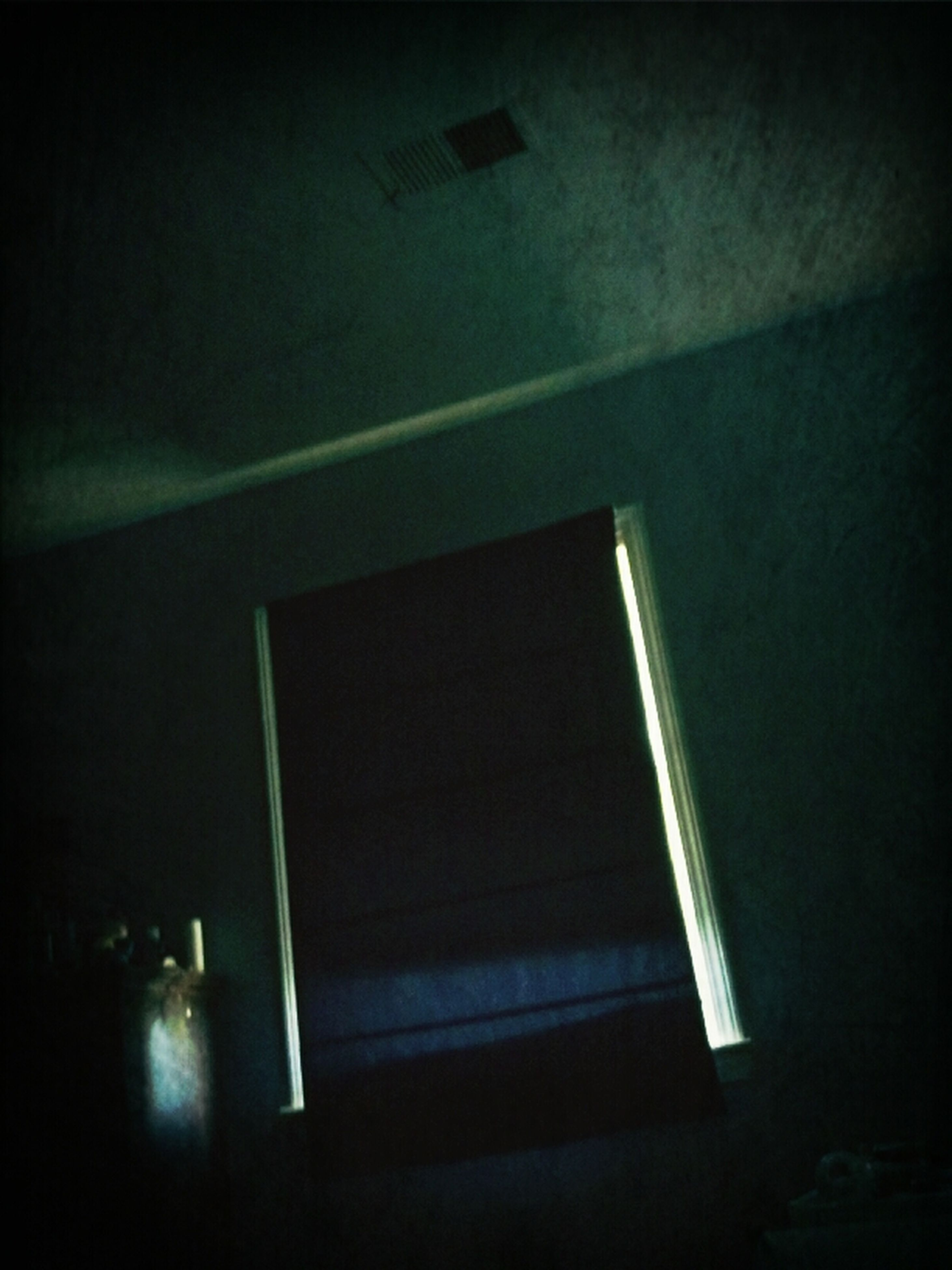 indoors, low angle view, illuminated, architecture, built structure, lighting equipment, window, wall - building feature, home interior, copy space, no people, wall, ceiling, dark, night, house, light - natural phenomenon, shadow, electric lamp, vignette