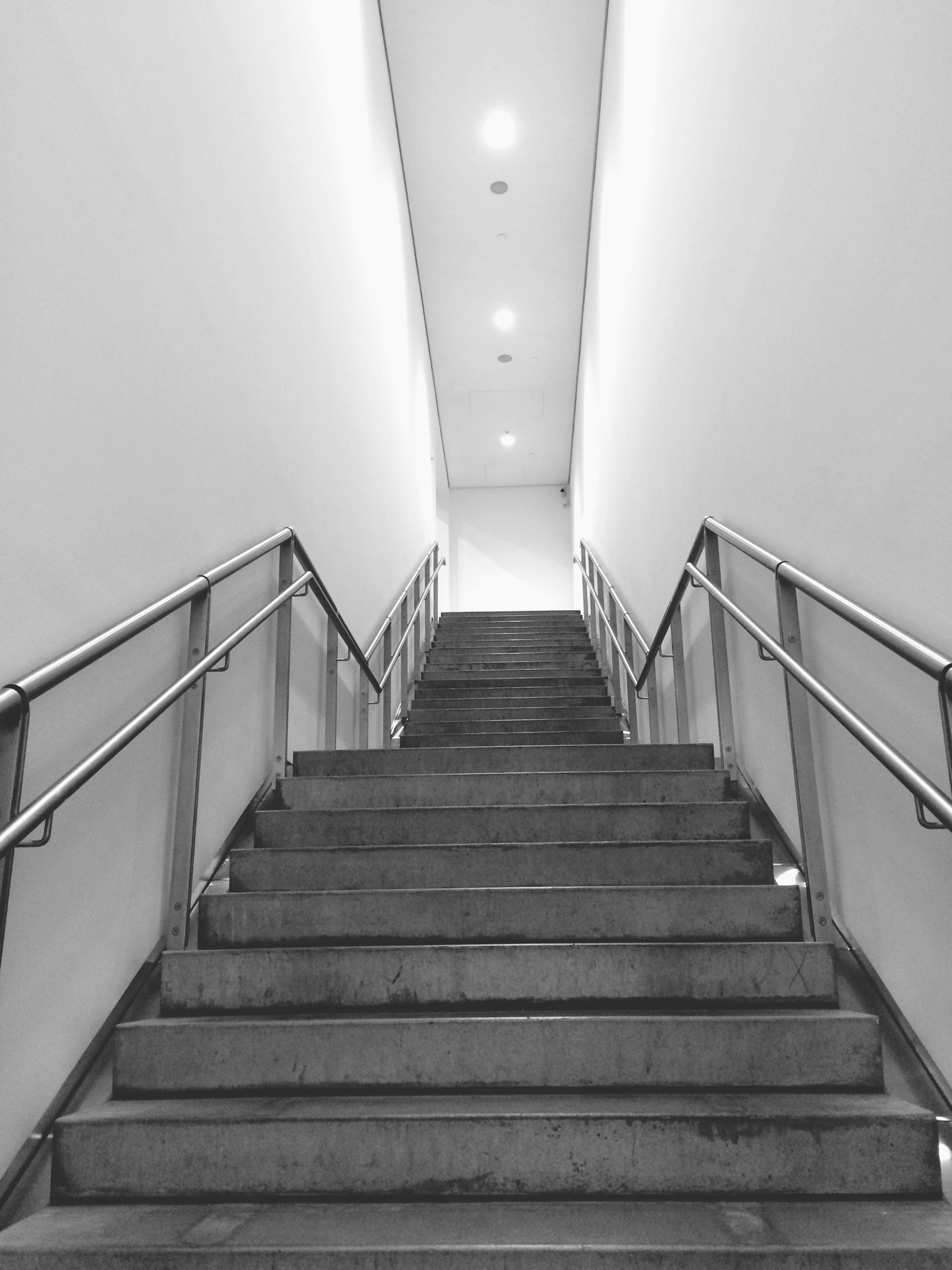 steps, architecture, steps and staircases, indoors, built structure, staircase, the way forward, railing, stairs, wall - building feature, corridor, diminishing perspective, building, low angle view, ceiling, wall, narrow, empty, absence, no people