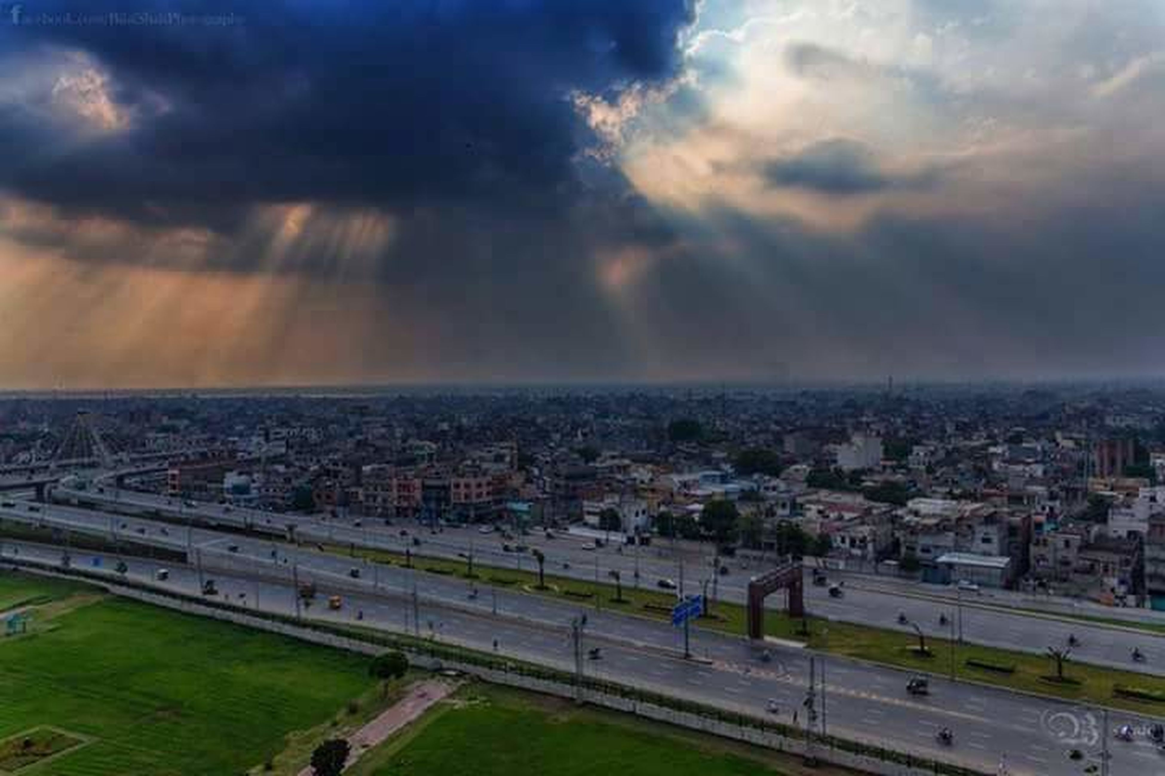 city, sunbeam, cityscape, road, architecture, cloud - sky, sky, scenics, cloud, day, outdoors, city life, horizon over land, tranquility, aerial view, beauty in nature, storm cloud, nature, cloudscape, dramatic sky, cloudy