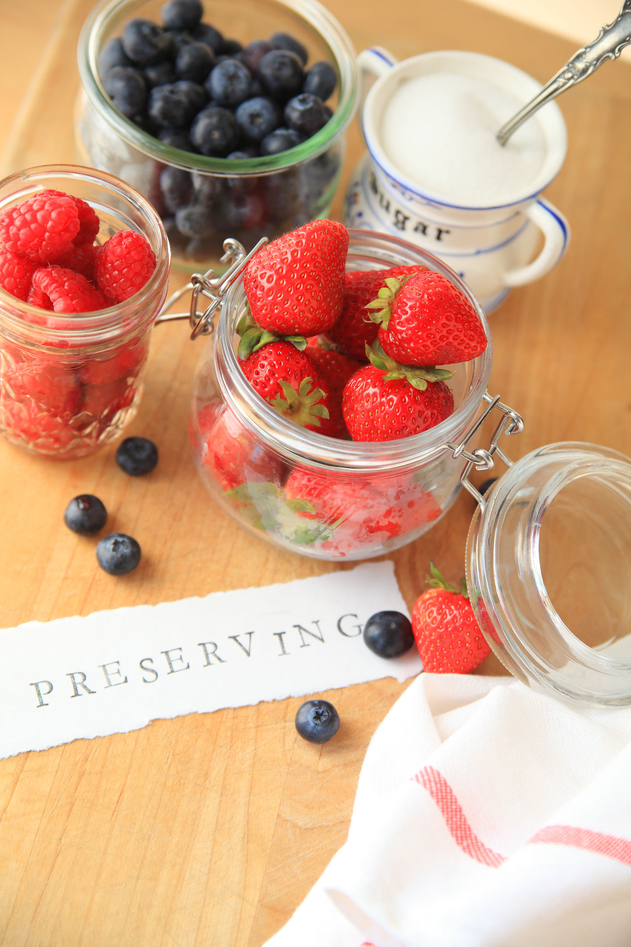 Preserving word with colorful berries Blueberries Close-up Dish Towel Fabric Food Ingredients Fresh Fruit Glass Jars Letters Making Jam Natural Light No People Overhead Preserving Food Raspberries Strawberries Sugar Summer Type Typography Wood - Material Word