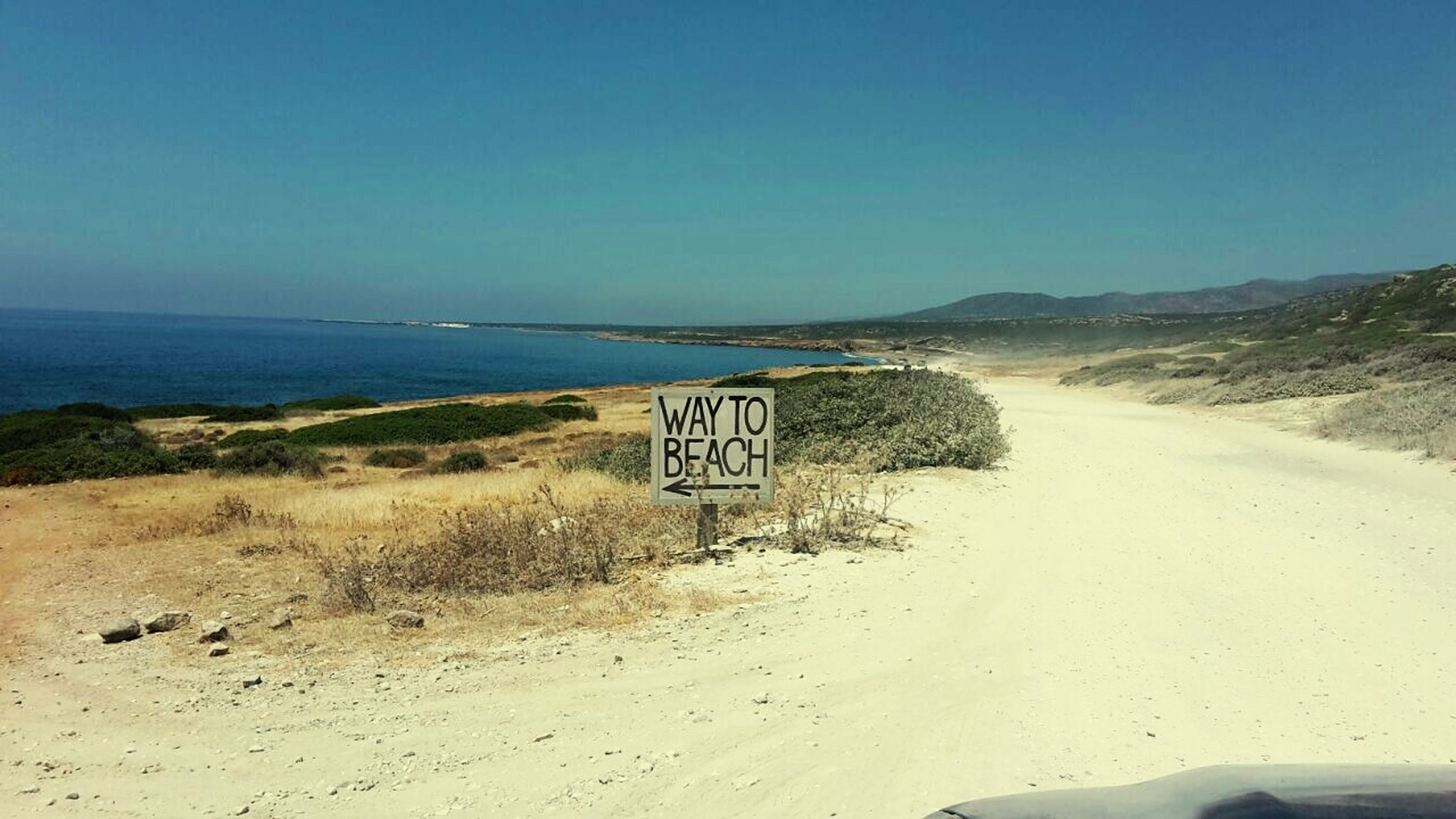 clear sky, text, western script, beach, tranquil scene, tranquility, sand, sea, communication, copy space, nature, scenics, information sign, blue, sign, road, water, guidance, sky, beauty in nature