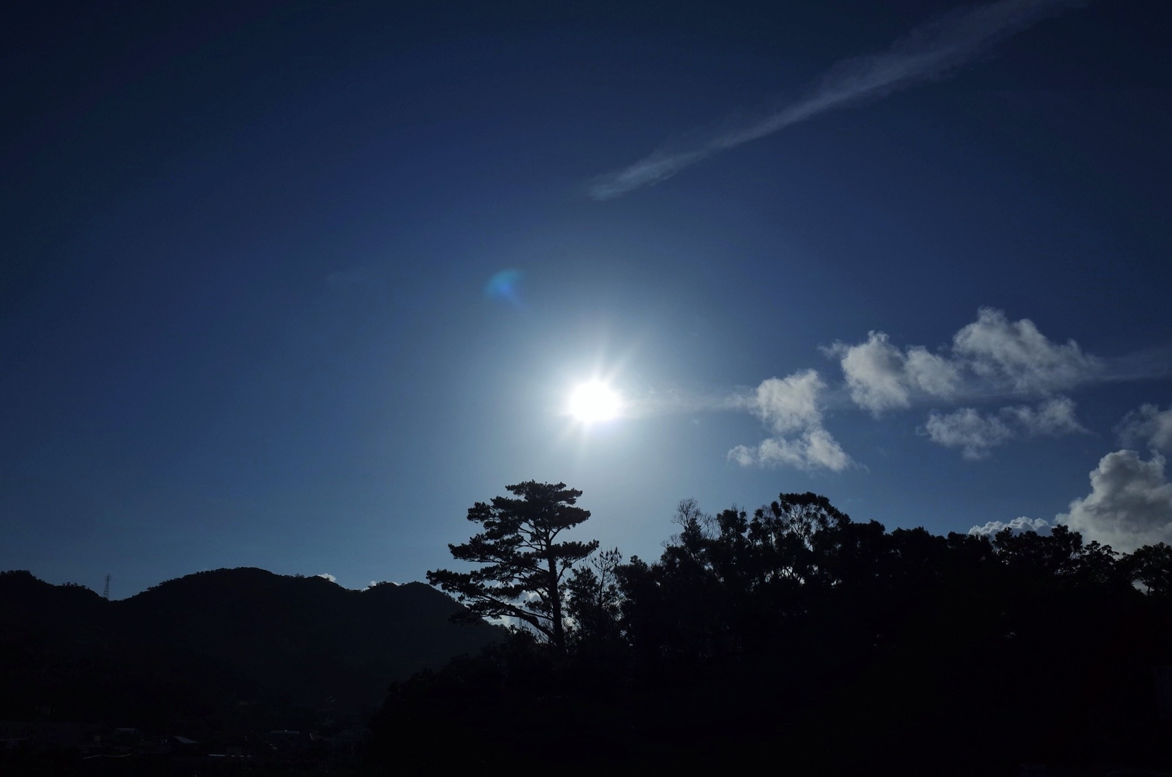 sun, tranquil scene, tranquility, scenics, beauty in nature, sunbeam, silhouette, sunlight, sky, mountain, tree, nature, lens flare, landscape, blue, idyllic, low angle view, non-urban scene, mountain range, outdoors