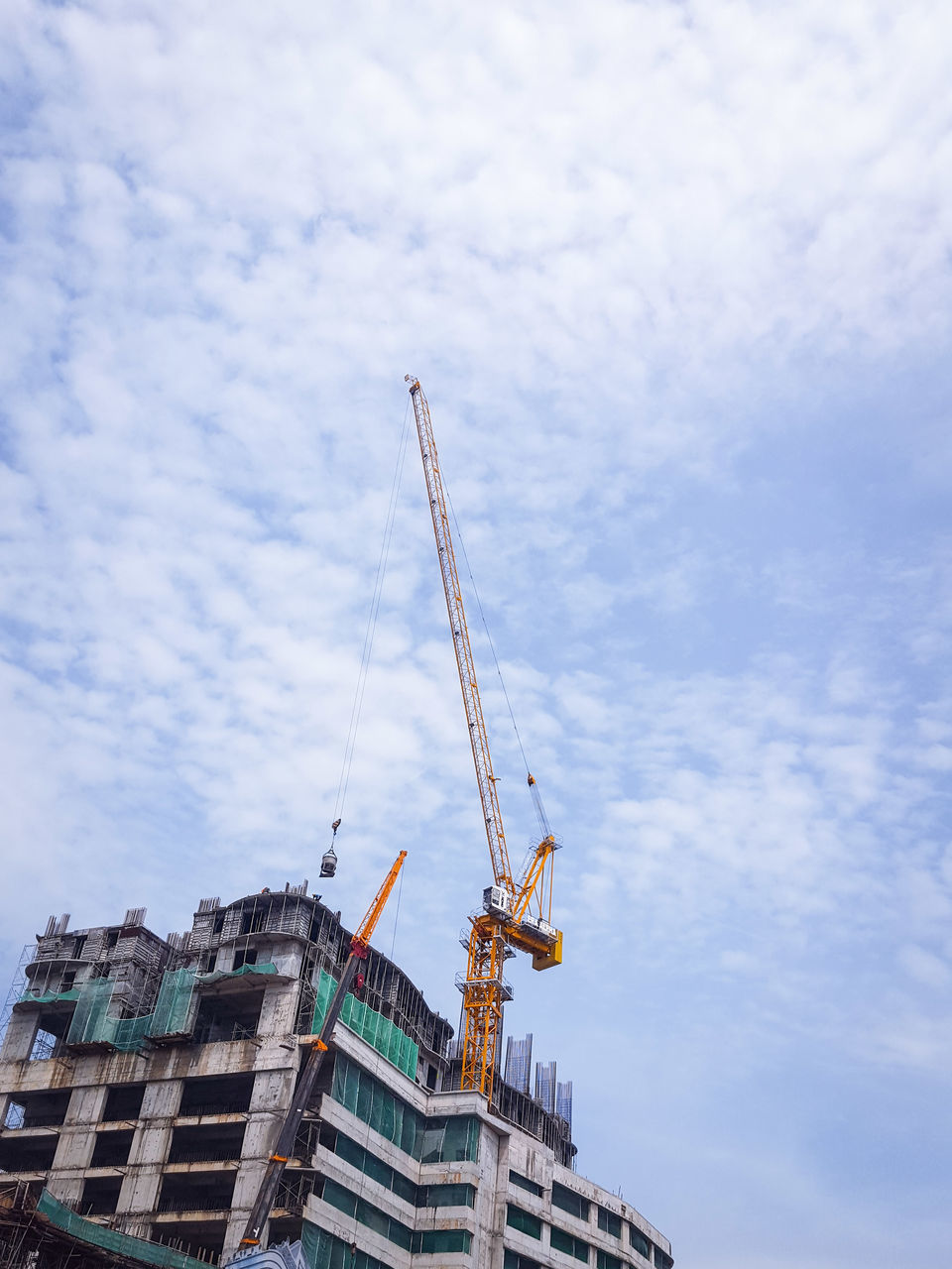 architecture, construction site, building exterior, construction, built structure, development, cloud - sky, sky, crane - construction machinery, low angle view, crane, building - activity, day, no people, progress, outdoors, city