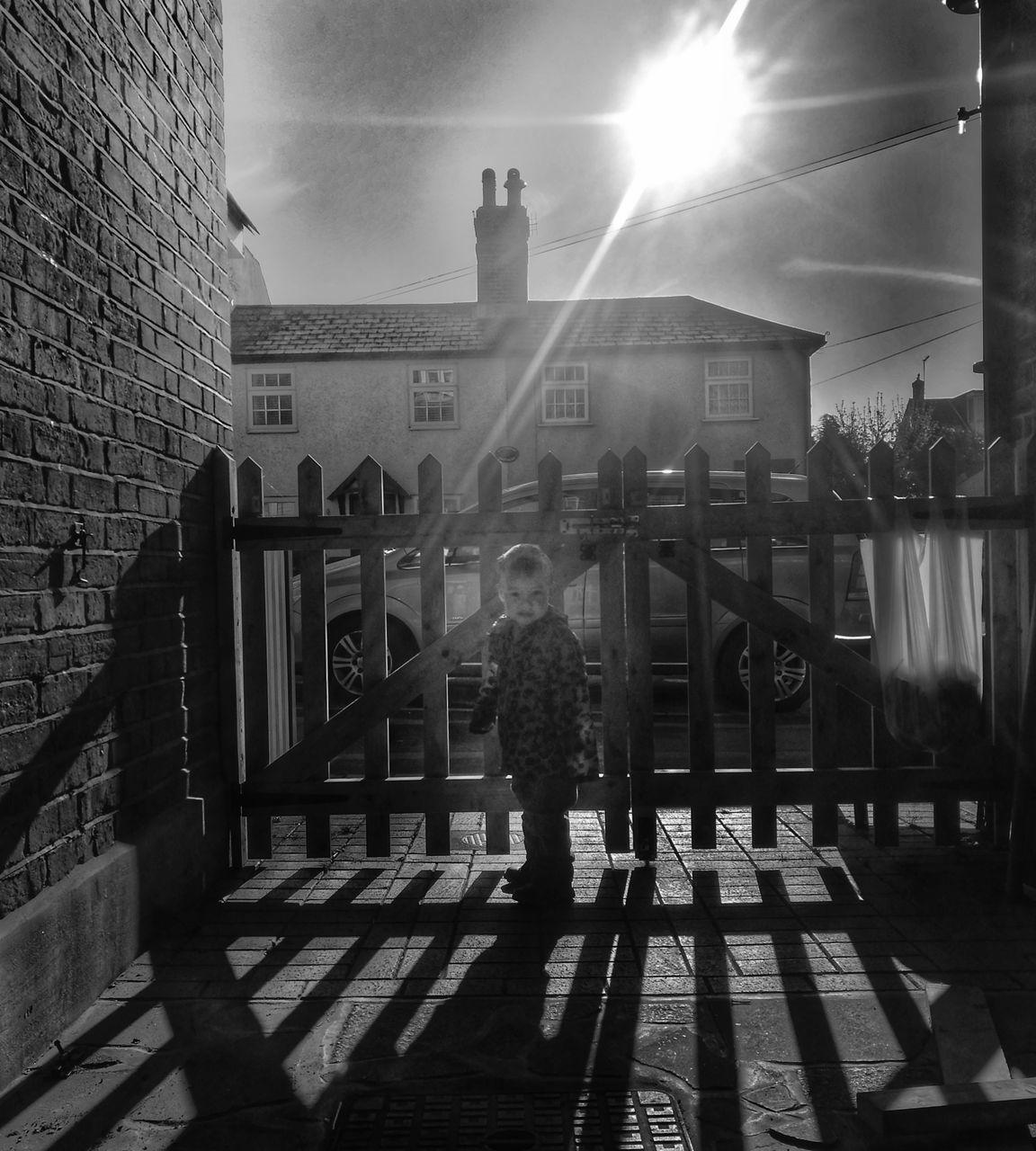 Portrait Of Boy Standing Against Gate