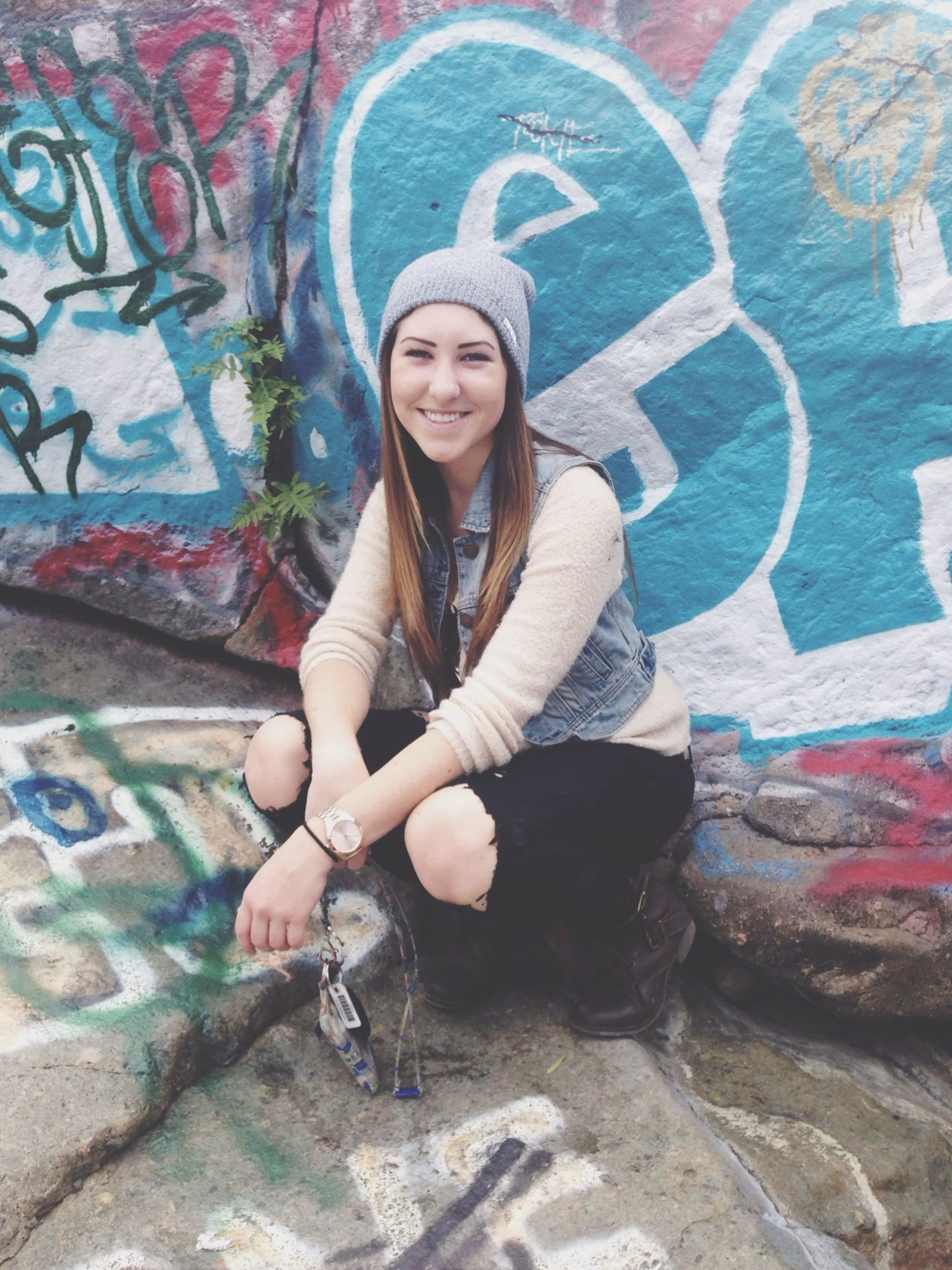 young adult, person, looking at camera, lifestyles, portrait, leisure activity, young women, casual clothing, smiling, front view, happiness, wall - building feature, standing, graffiti, full length, long hair, three quarter length