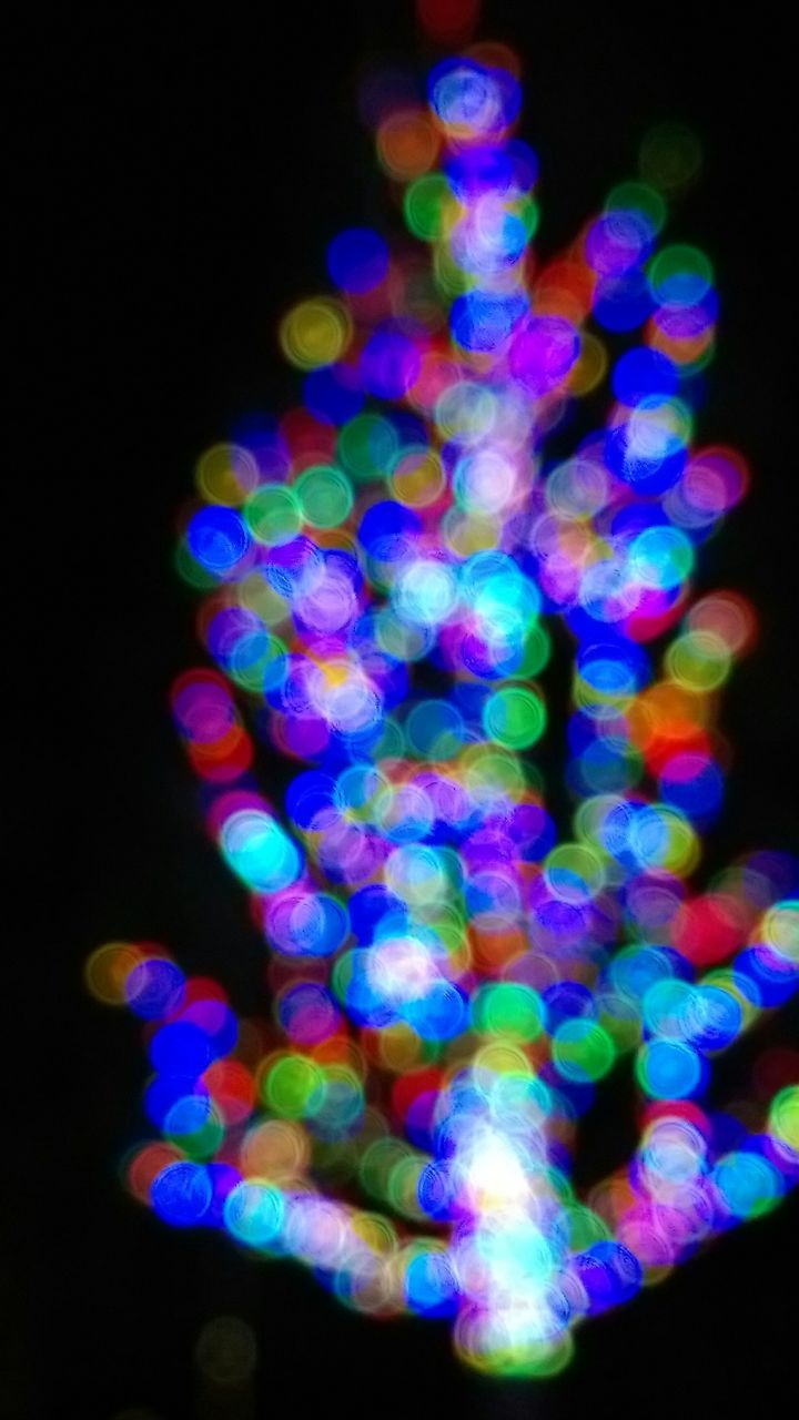 Defocused Image Of Colorful Christmas Lights On Tree At Home