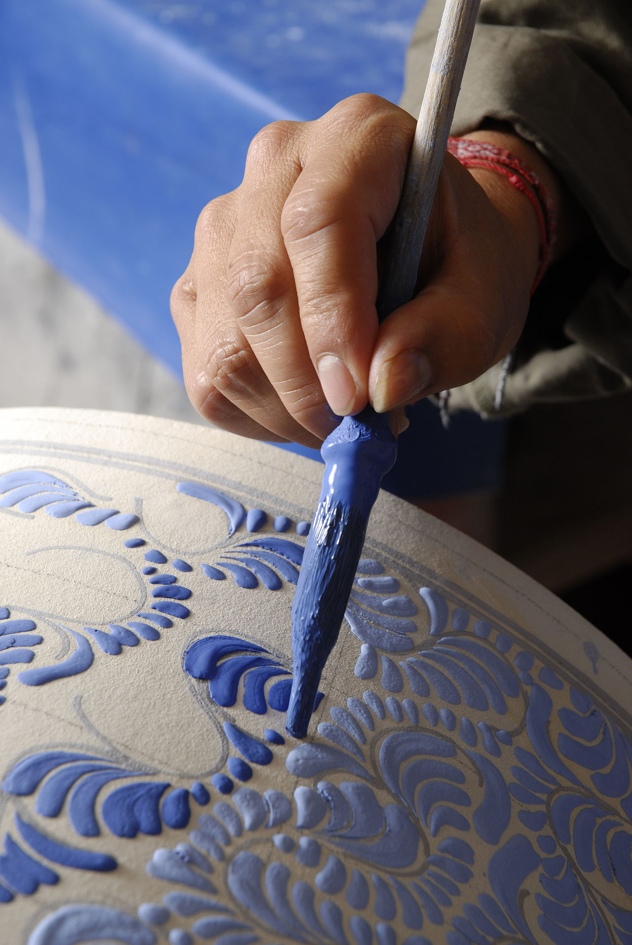 Talavera pottery being painted Art Skills Blue Close-up Hand Painting Holding Human Body Part Human Hand Mexican Handcraft Occupation One Person Outdoors People Popular Art Real People Sand Skill  Working