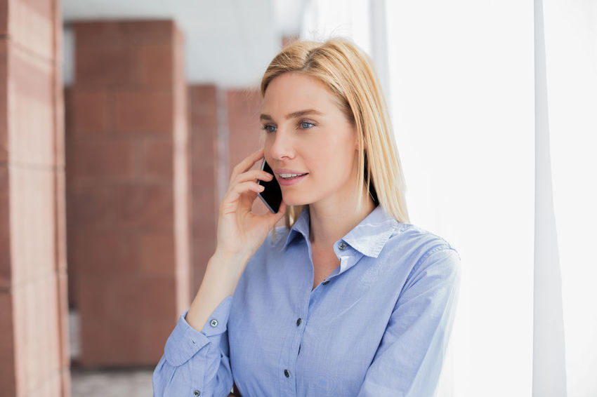 Answering Blond Hair Built Structure Business Businesswoman Cheerful Communication Connection Front View Happiness Holding Indoors  Listening Mobile Phone One Person One Woman Only Only Women Portable Information Device Smiling Talking Technology Telephone Using Phone Wireless Technology Women