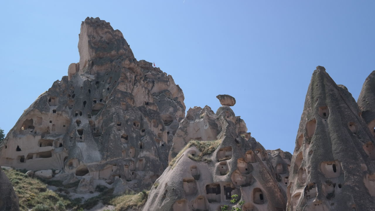 history, low angle view, rock - object, ancient, travel destinations, old ruin, day, architecture, built structure, outdoors, clear sky, no people, mountain, building exterior, spirituality, ancient civilization, sky, nature