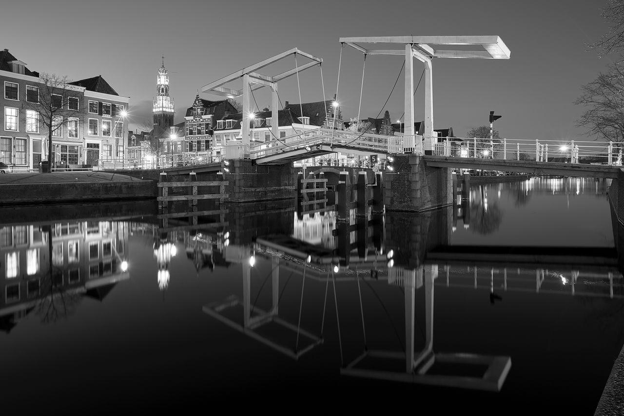 Reflection Of Illuminated Bridge Over River At Dusk