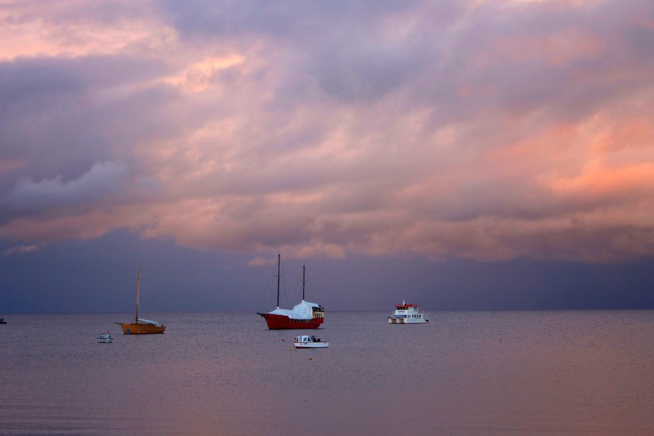 Boats On Sea Against Cloudy Sky During Sunset