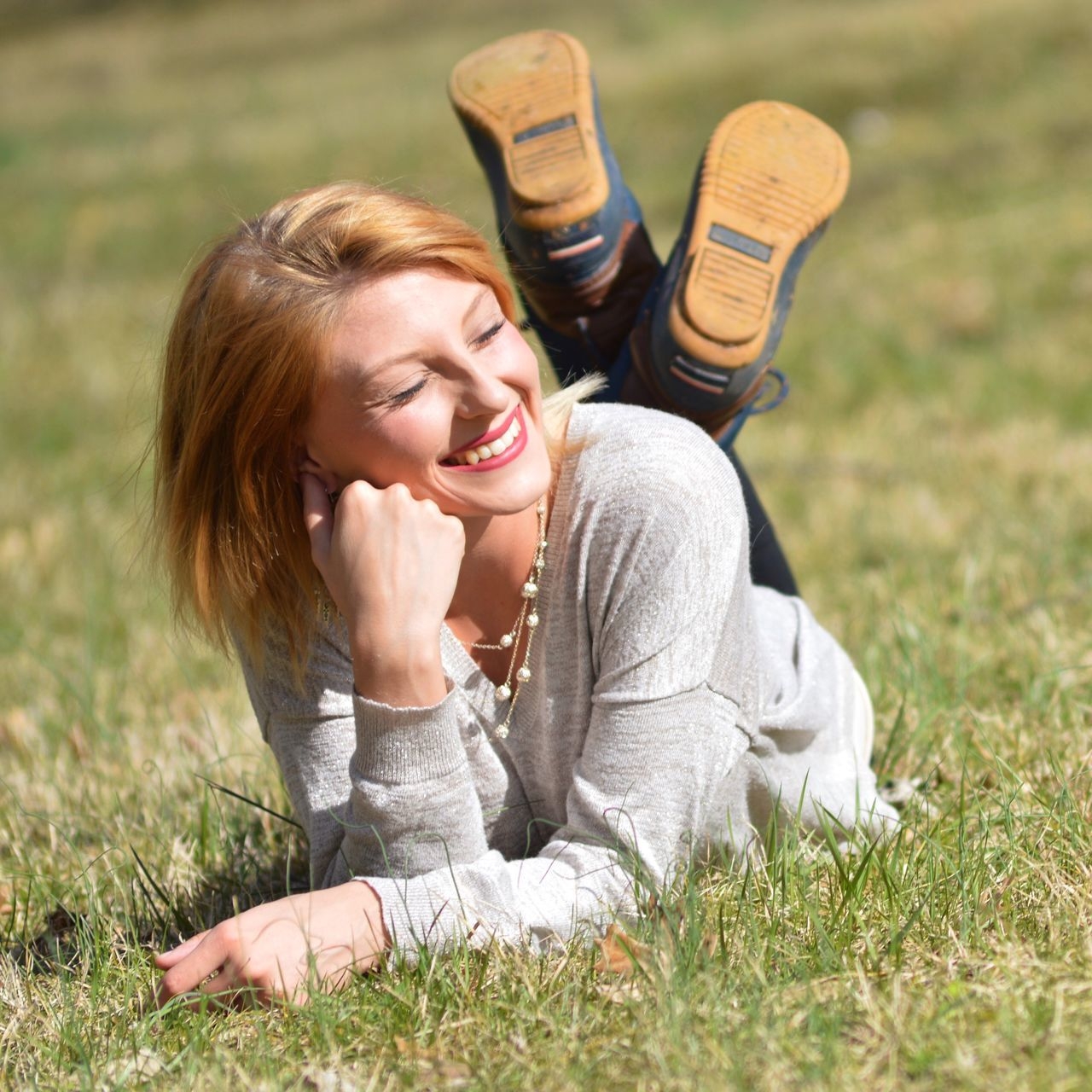 grass, leisure activity, casual clothing, young adult, one person, smiling, day, young women, happiness, outdoors, real people, sitting, relaxation, lying down, lifestyles, nature, low section, blond hair, close-up, people