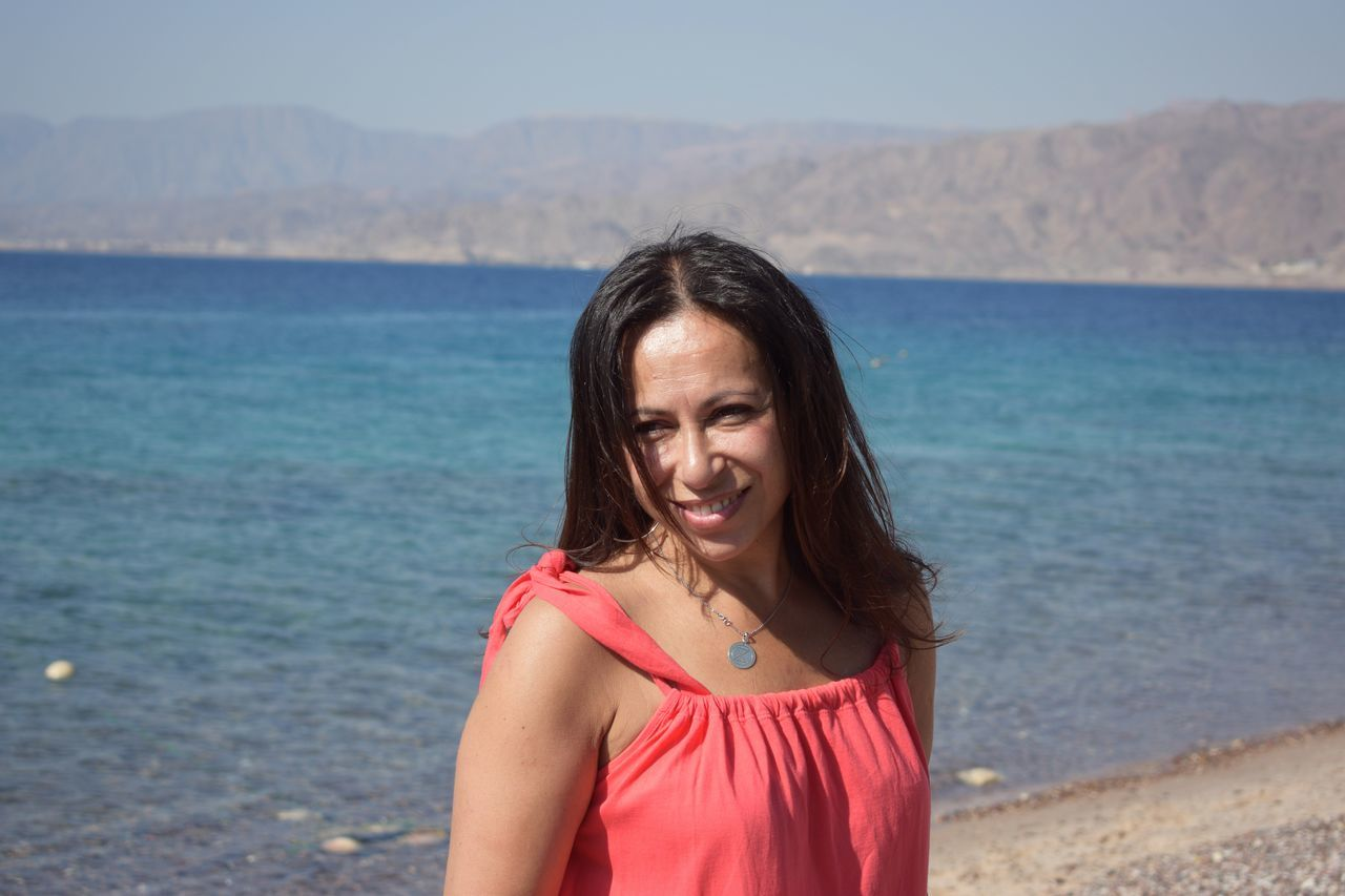 Portrait Of Happy Woman At Beach Against Mountains