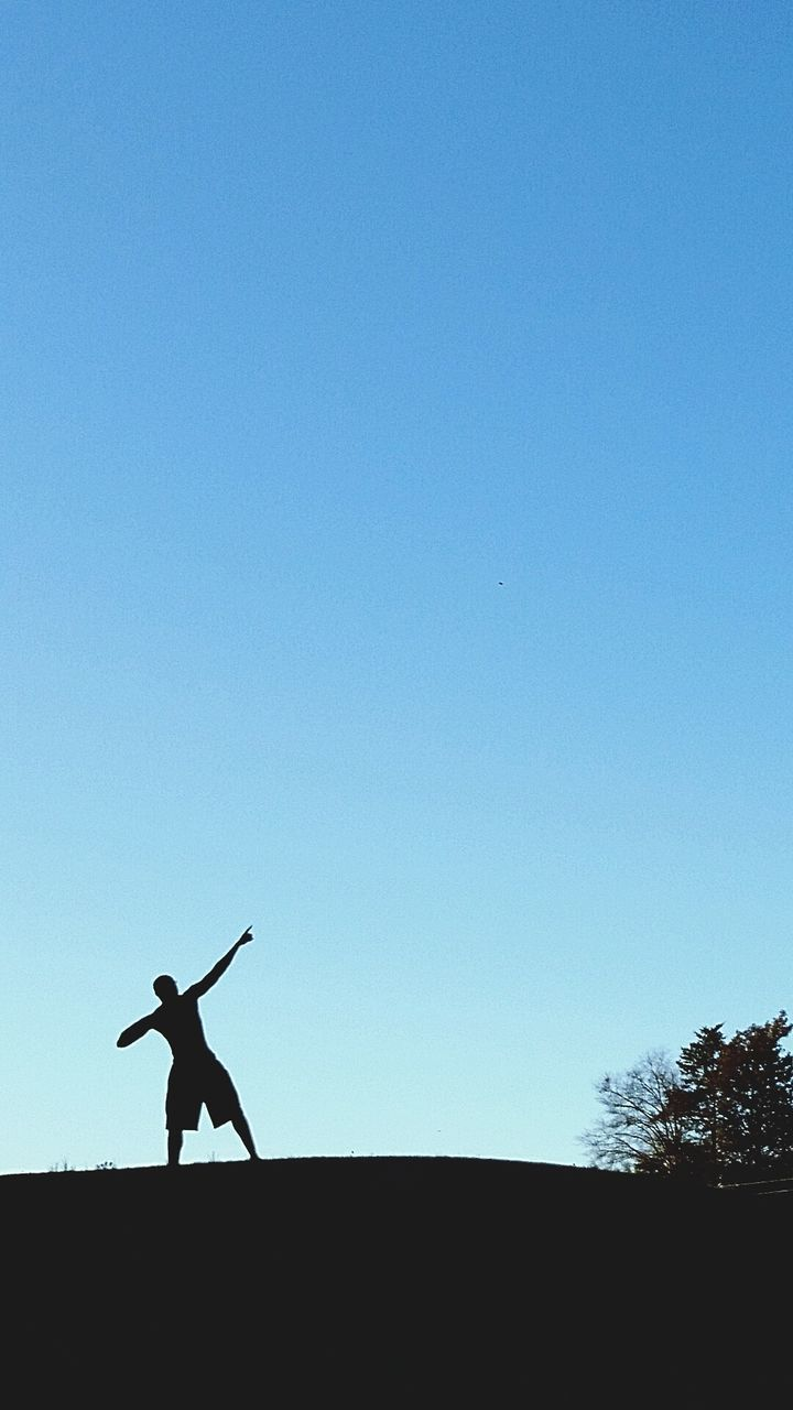 copy space, clear sky, silhouette, blue, one person, full length, men, skill, day, leisure activity, lifestyles, outdoors, real people, golf, energetic, sky, young adult, golfer, people