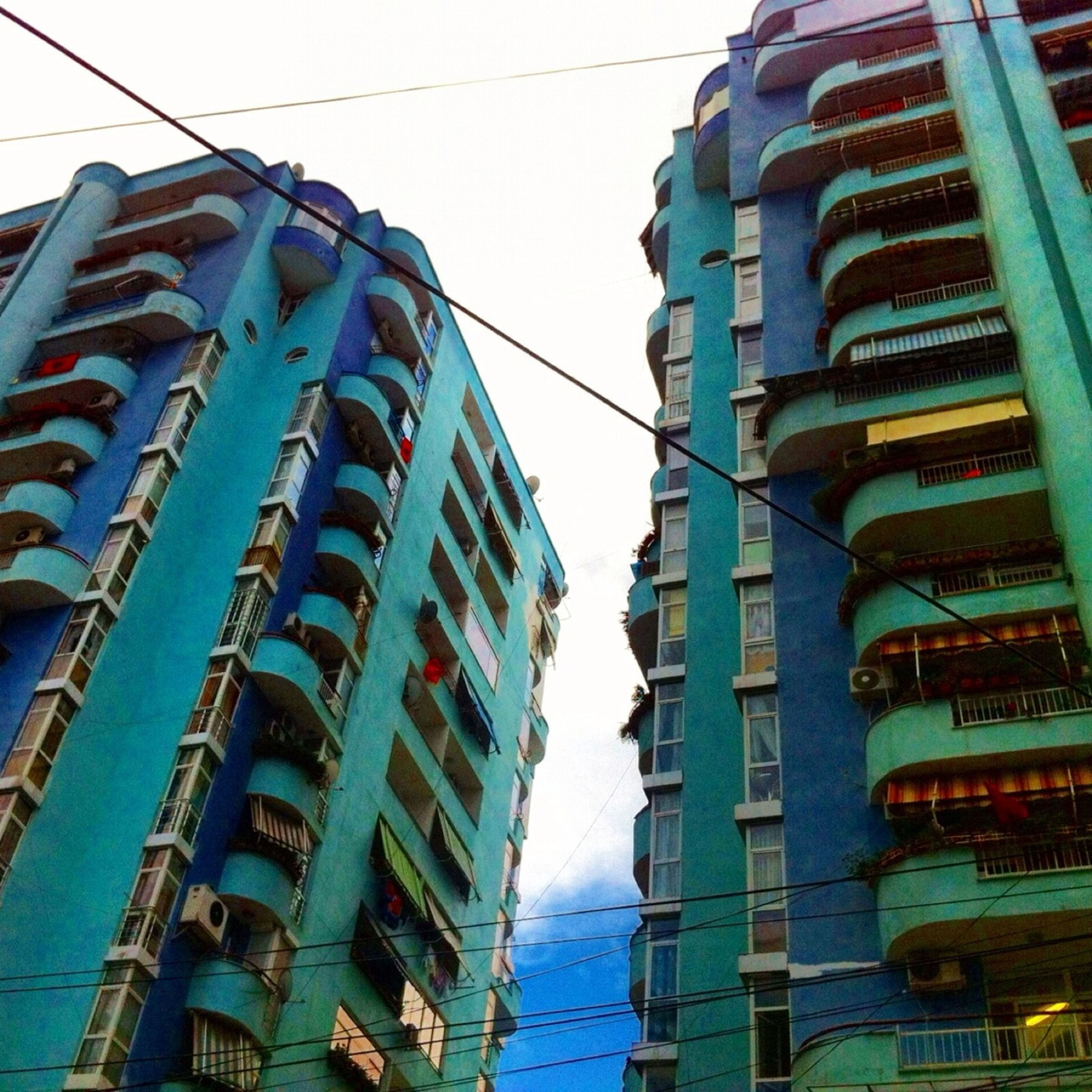 architecture, building exterior, built structure, low angle view, sky, building, city, residential building, day, window, in a row, outdoors, residential structure, no people, reflection, clear sky, city life, blue, modern, cable
