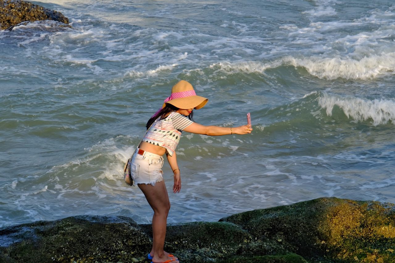 real people, sea, leisure activity, lifestyles, one person, beach, nature, full length, standing, outdoors, water, day, vacations, beauty in nature, young adult, wave, camera - photographic equipment, young women, technology, photography themes, ankle deep in water, sky, people