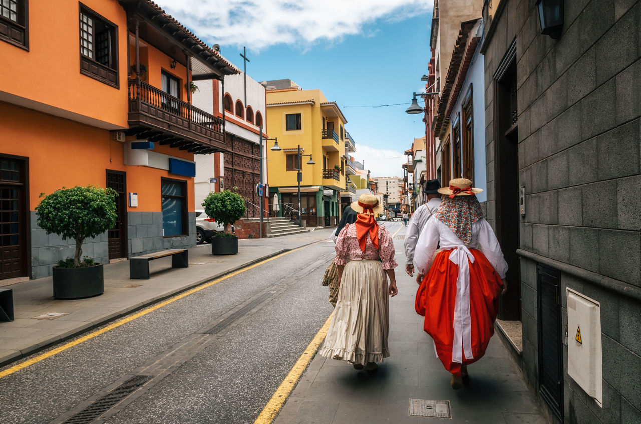 A group of locals in Canarian traditional clothes walk along the street of Puerto de la Cruz with colorful houses. Celebration of the Day of Canary Islands. View from the back. Tenerife, 30 may, Spain Architecture Building Exterior Built Structure Canary Islands Celebration Festival Lifestyles Men Outdoors People Real People Rear View Street Tenerife Traditional Clothing Walking Women The Street Photographer - 2017 EyeEm Awards Let's Go. Together.