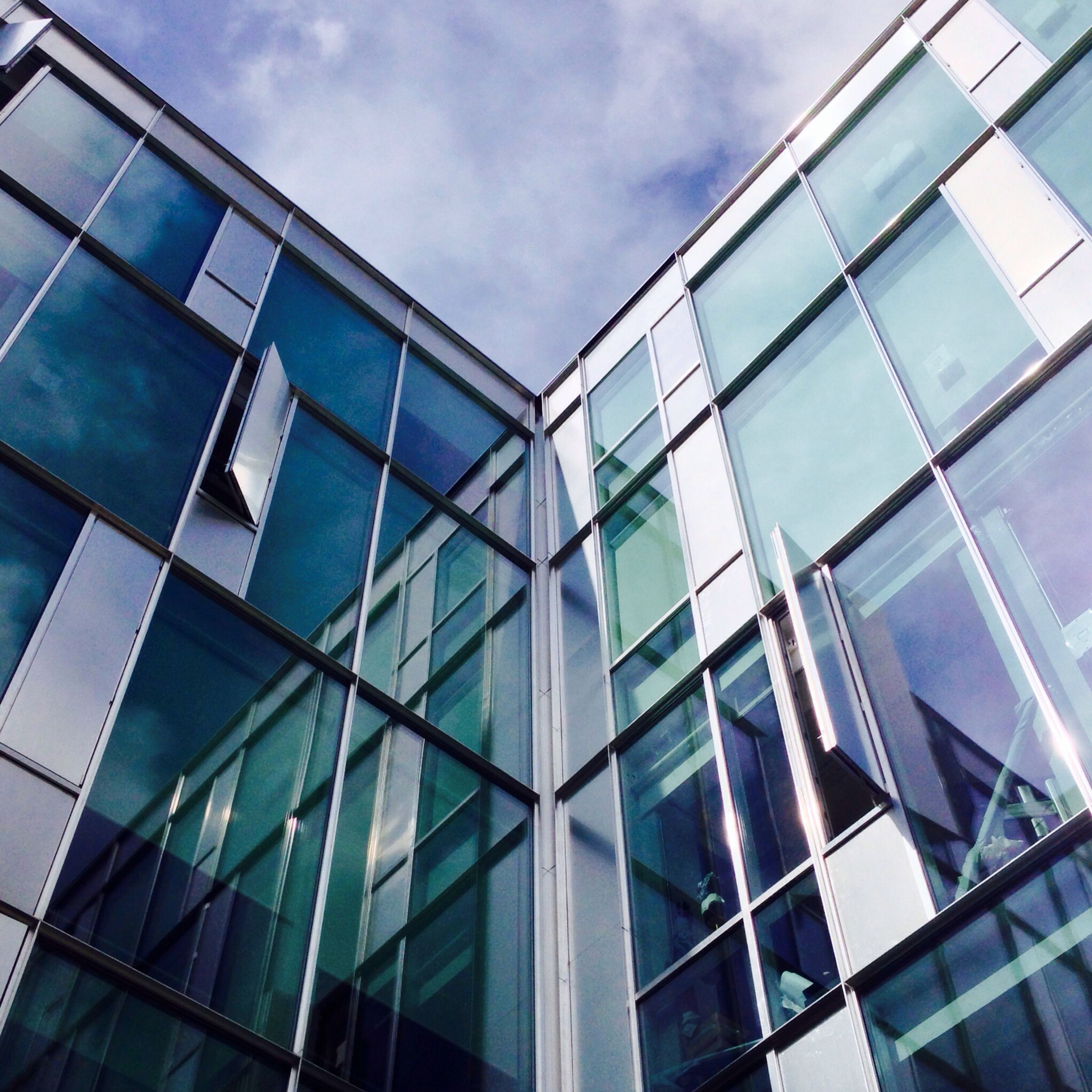 architecture, building exterior, built structure, modern, low angle view, glass - material, office building, reflection, window, city, skyscraper, building, glass, sky, tall - high, transparent, tower, day, cloud - sky, no people