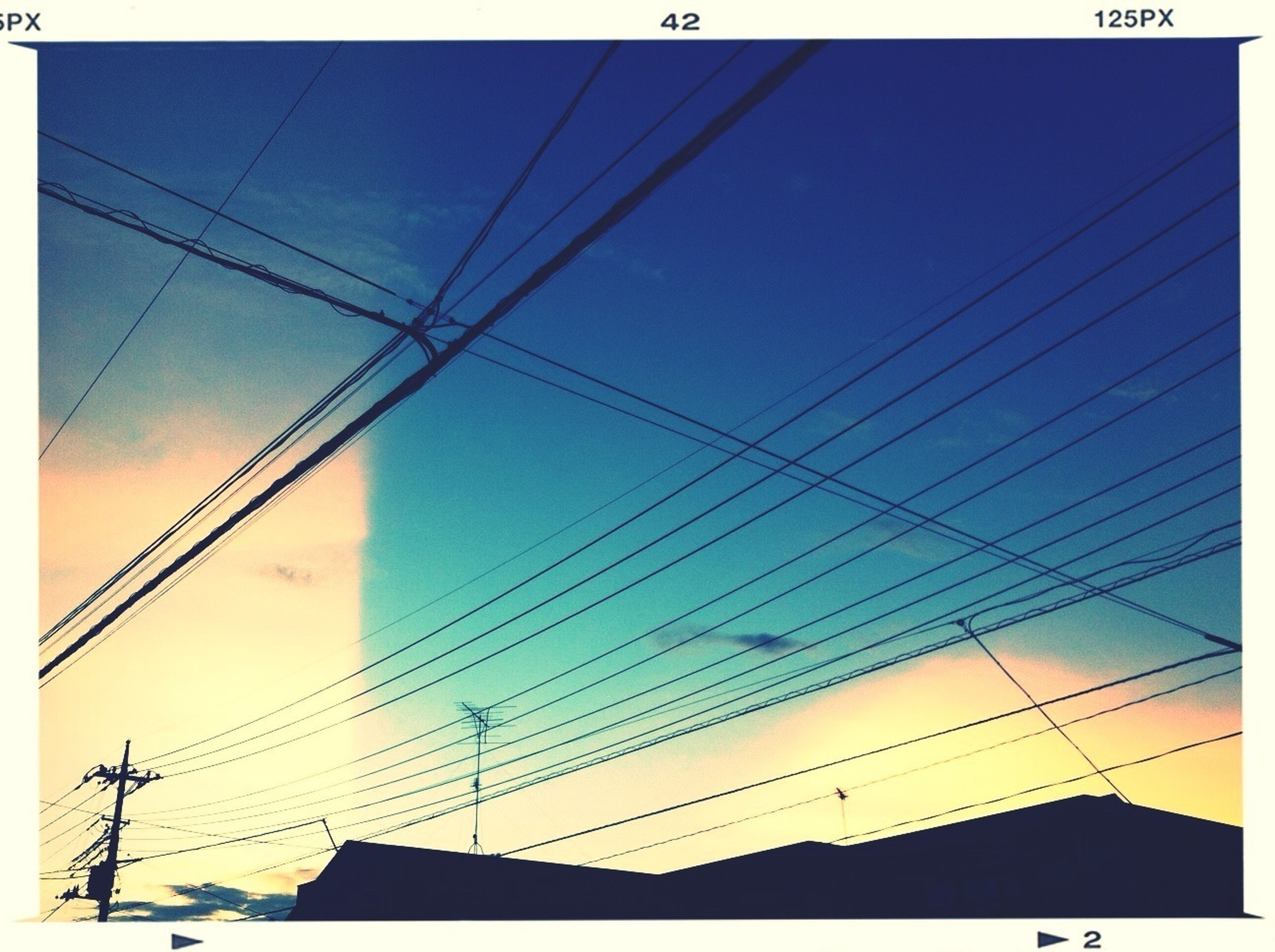 power line, low angle view, cable, electricity pylon, power supply, electricity, connection, built structure, architecture, sky, building exterior, power cable, fuel and power generation, silhouette, technology, cloud - sky, cloud, high section, blue, outdoors