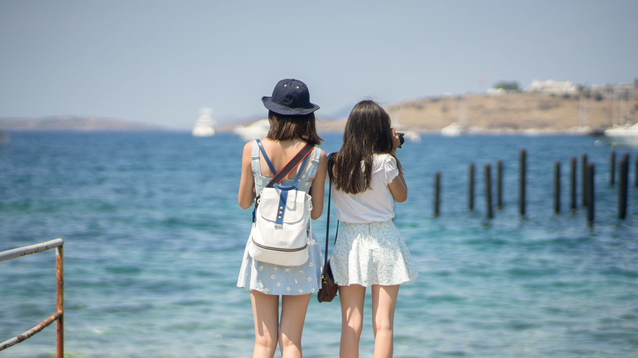 Two young lady tourists are standing in front of Aegean Sea and taking photos under strong summer sunlight at Bodrum, Turkey. 16:9 Aegean Bag Bodrum Camera Cap Girls Lady Lifestyle People Photographing Ruins Sea Skirt Standing Sunlight Taking Photos Tourists Turkey Two Water Women Young Adult
