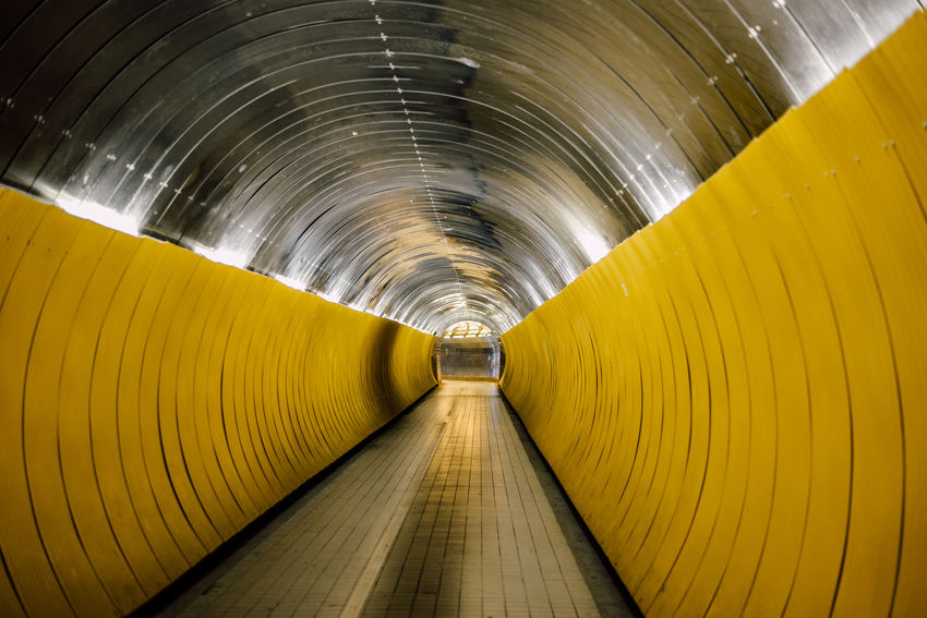 Passage between roads thru a tunnel with metal sheets in yellow and silver Bike Bike Lane Deminishing Perspective Metal Tunnel Vanishing Point Walking Tunnel Yellow