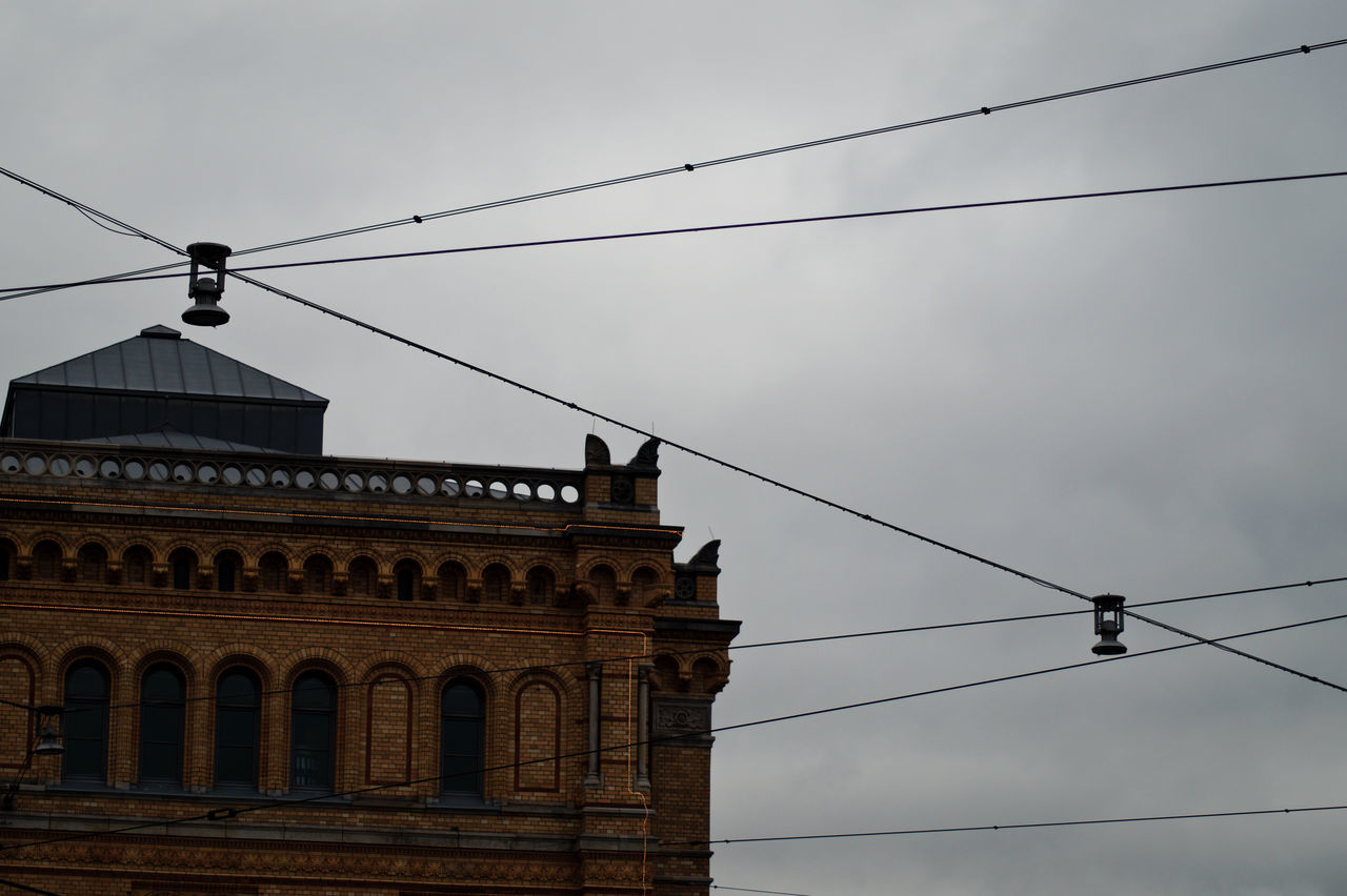 Low Angle View Of Building And Cables Against Cloudy Sky