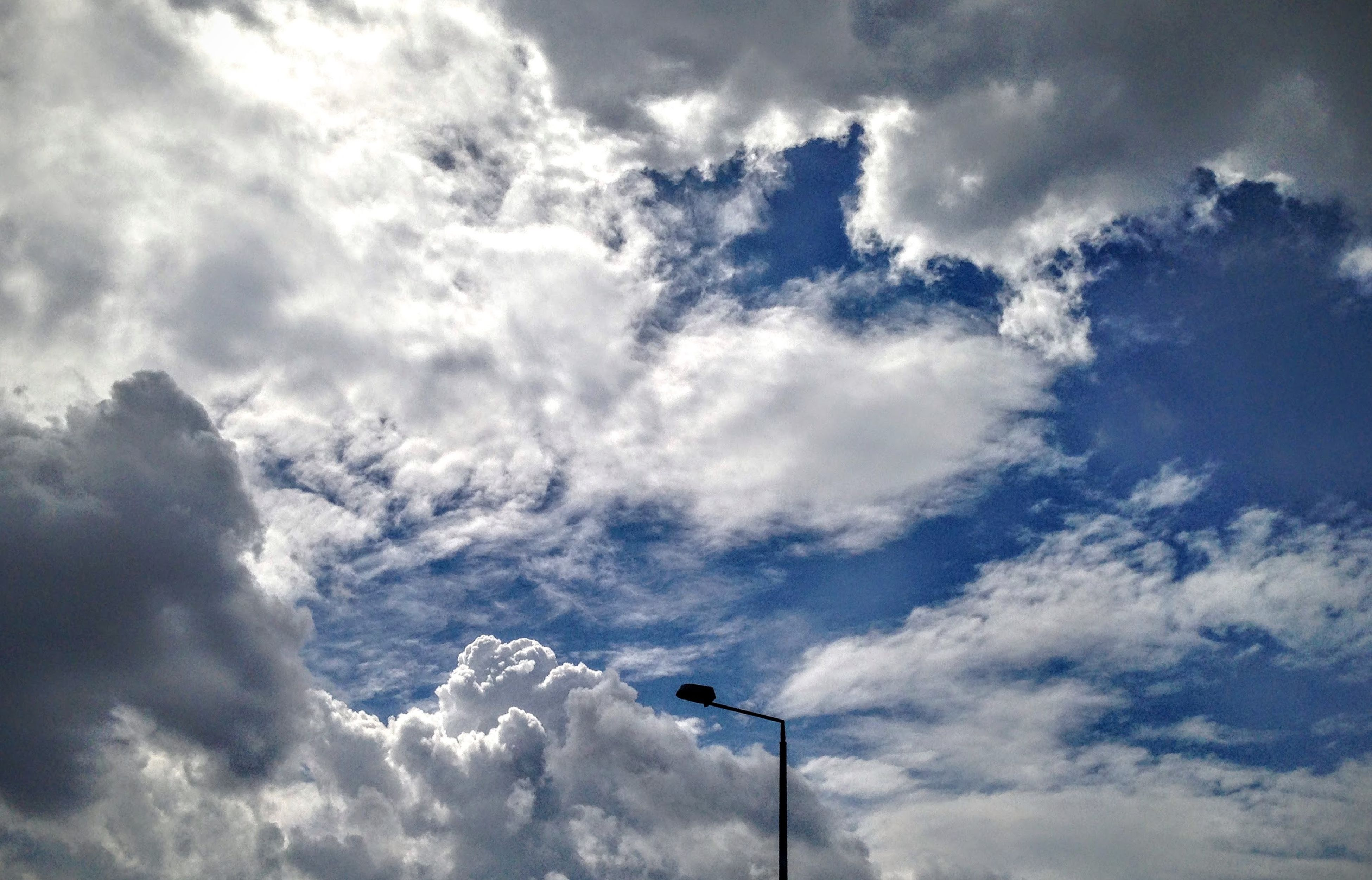 low angle view, sky, cloud - sky, cloudy, cloud, beauty in nature, tranquility, nature, weather, scenics, cloudscape, tranquil scene, day, outdoors, no people, overcast, blue, white, idyllic, high section, backgrounds