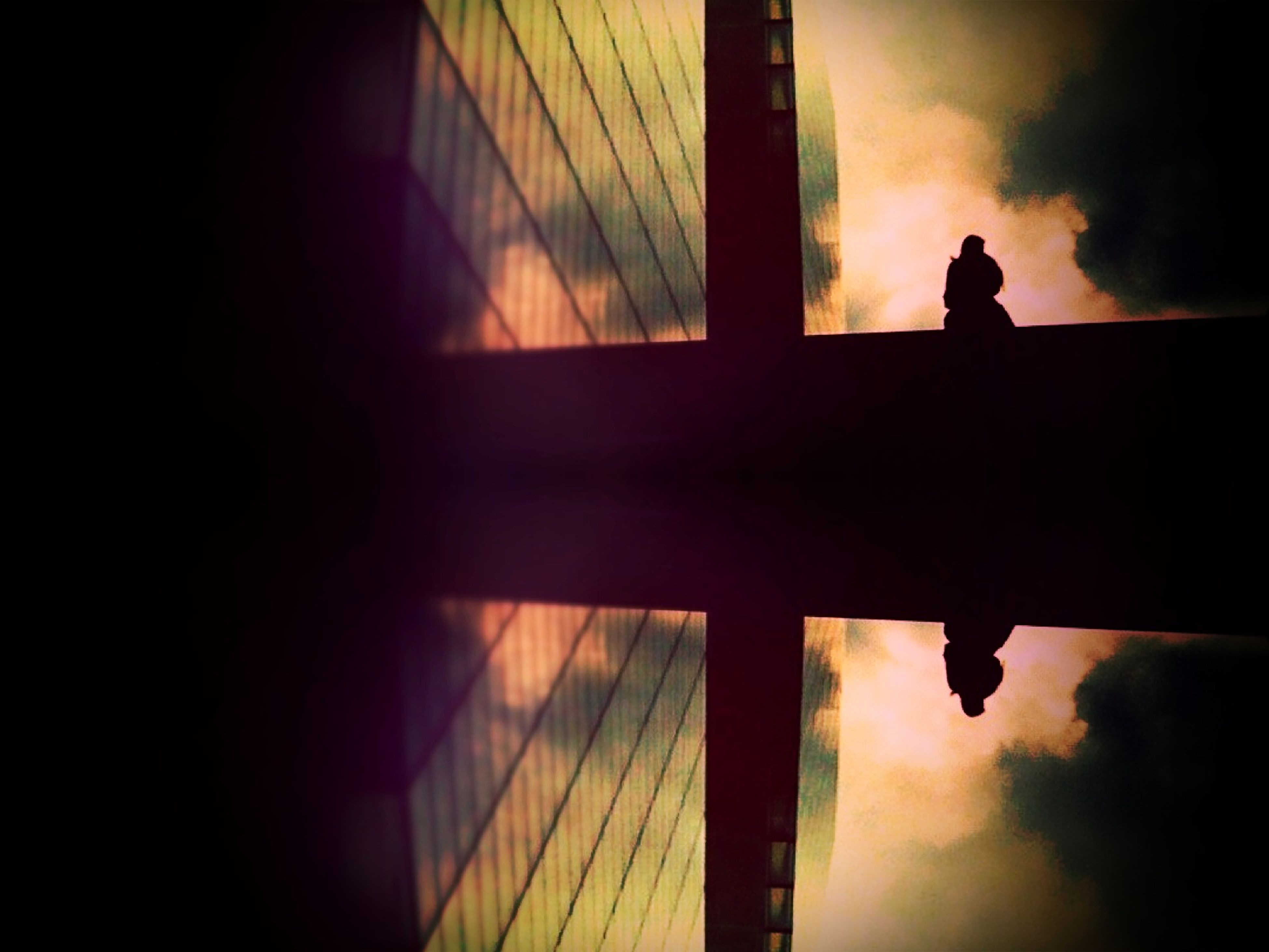 silhouette, sunset, sky, outline, low angle view, built structure, architecture, dusk, cloud - sky, one person, reflection, dark, indoors, cloud, railing, sunlight, standing, orange color, nature