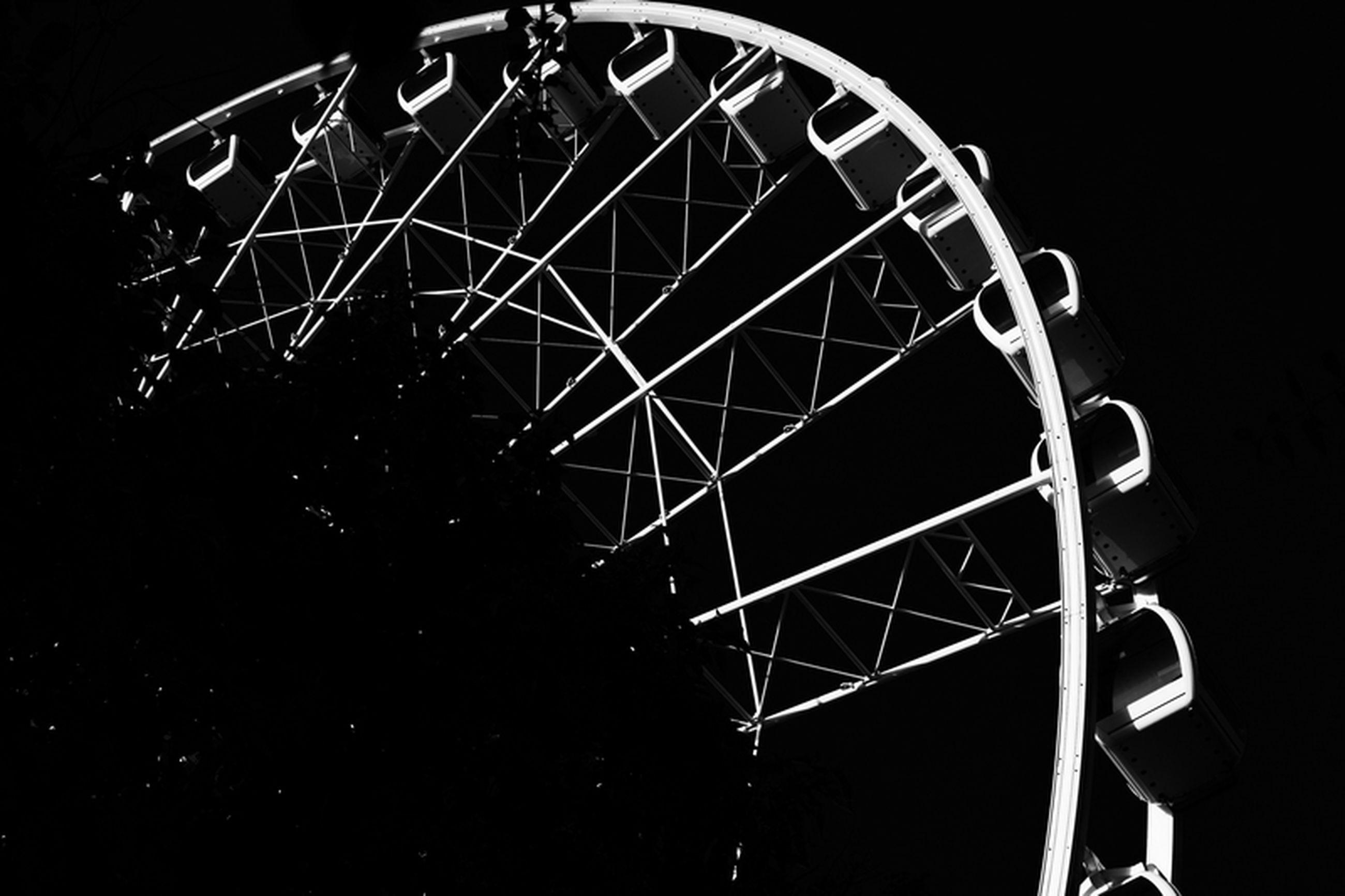 low angle view, ferris wheel, arts culture and entertainment, amusement park, metal, amusement park ride, night, circle, illuminated, built structure, metallic, geometric shape, clear sky, no people, sky, pattern, outdoors, architecture, shape