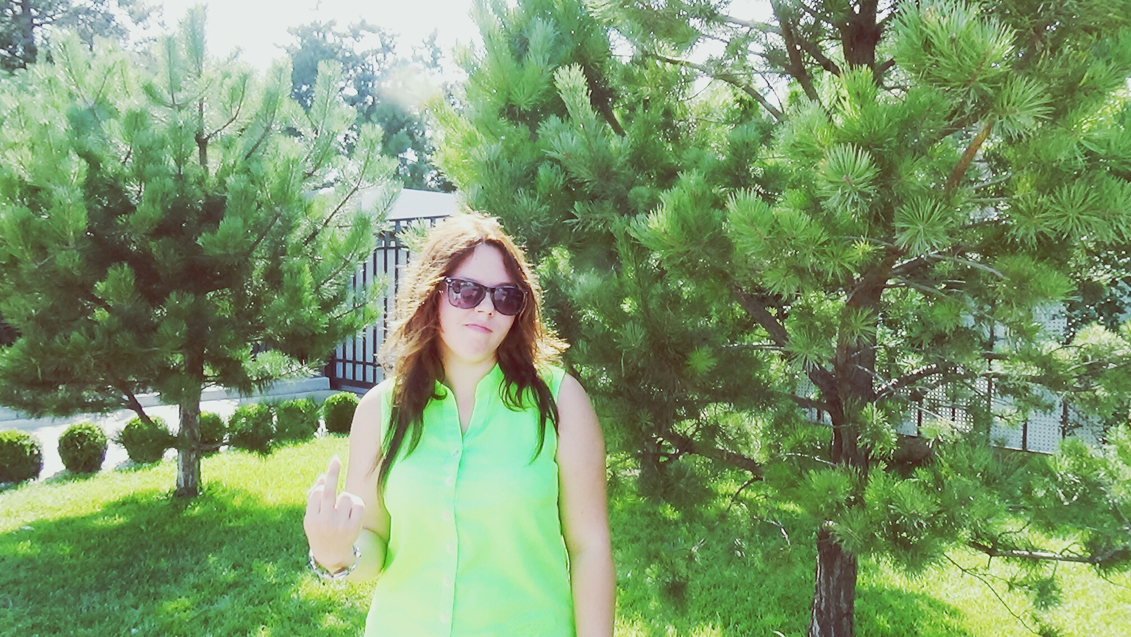 lifestyles, tree, young adult, leisure activity, person, young women, casual clothing, long hair, standing, growth, green color, waist up, three quarter length, front view, plant, looking at camera, park - man made space, smiling