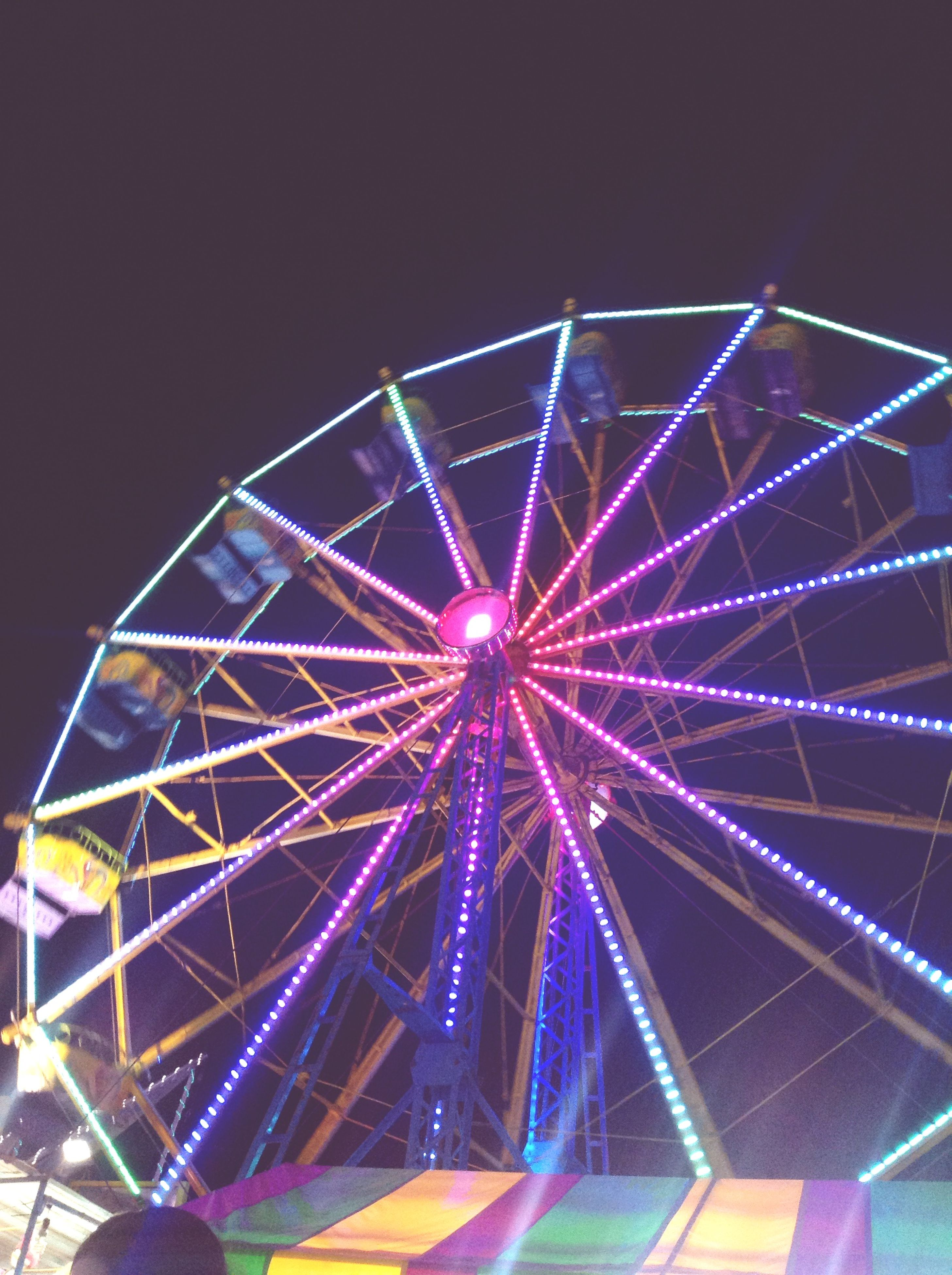 illuminated, arts culture and entertainment, night, amusement park ride, amusement park, ferris wheel, low angle view, sky, multi colored, built structure, clear sky, lighting equipment, fun, architecture, outdoors, glowing, motion, enjoyment, no people, long exposure