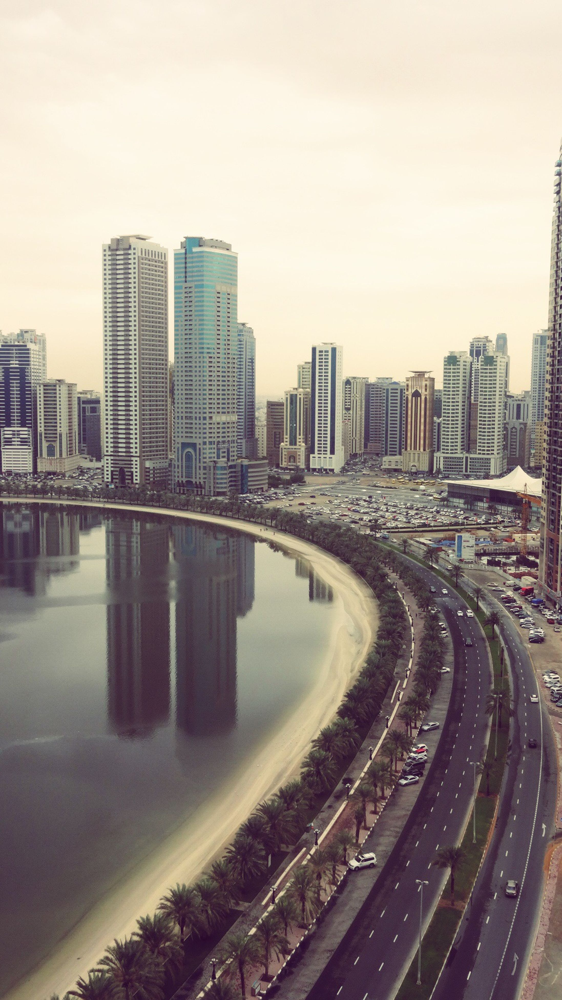 architecture, built structure, building exterior, city, cityscape, water, river, transportation, sky, skyscraper, city life, connection, modern, bridge - man made structure, road, street, high angle view, building, outdoors, clear sky