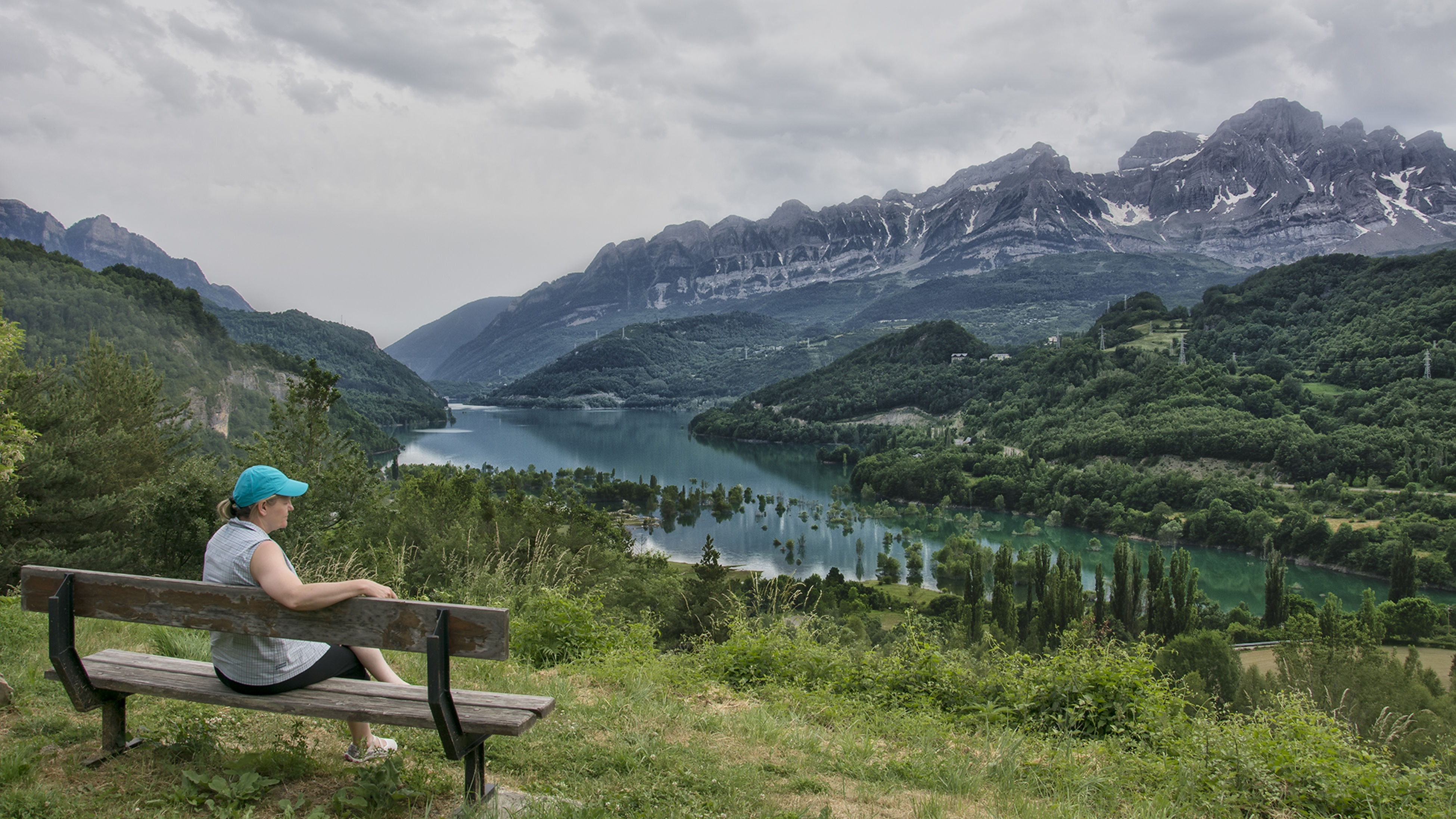 mountain, nature, real people, water, beauty in nature, scenics, lake, day, one person, sitting, tranquil scene, sky, tranquility, outdoors, lifestyles, leisure activity, mountain range, landscape, full length, tree