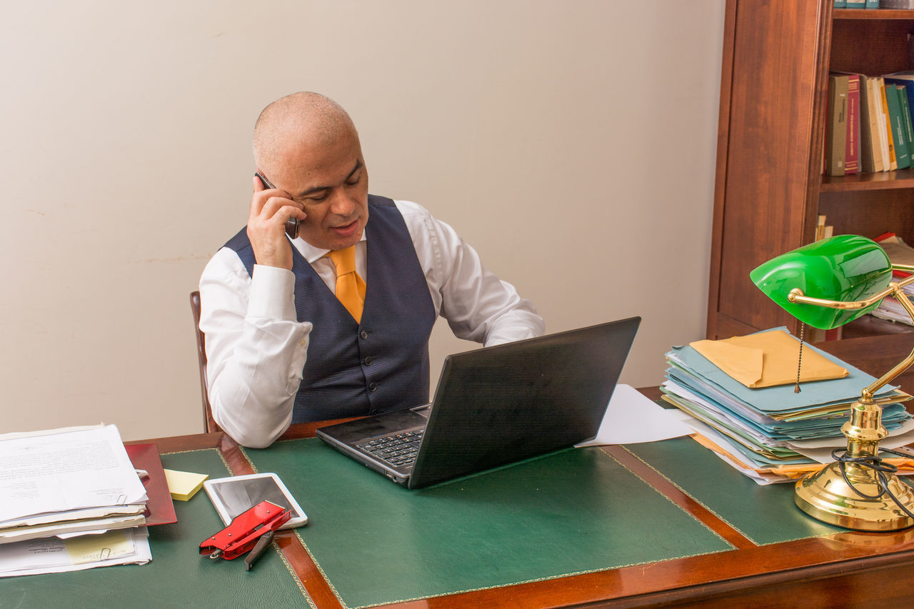 Adult Adults Only Business Businessman Businesswear Communication Desk Formal Businesswear Hair Loss Laptop Looking Down Men Office One Man Only One Person Only Men Paperwork Portability Shaved Head Sitting Technology Using Laptop Well-dressed Wireless Technology Working