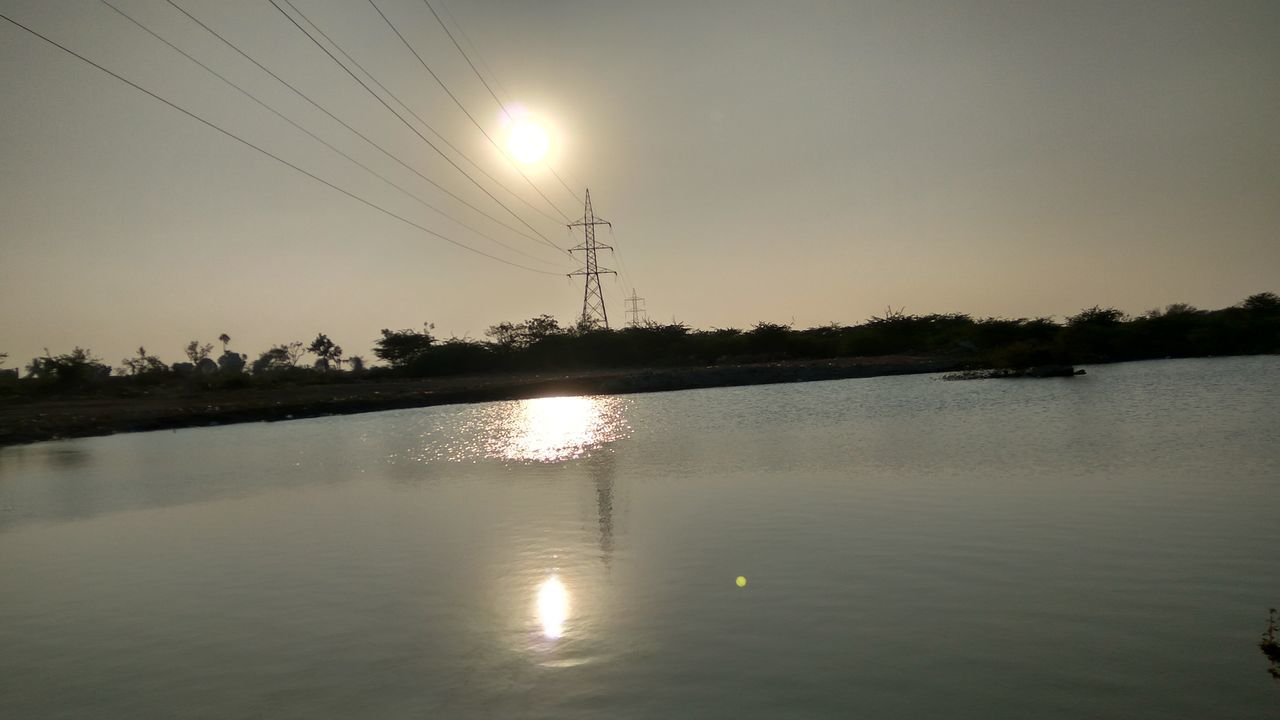 cable, electricity pylon, power line, reflection, electricity, sun, power supply, fuel and power generation, water, sky, no people, connection, waterfront, sunset, tree, lake, outdoors, nature, built structure, clear sky, technology, beauty in nature, architecture, day