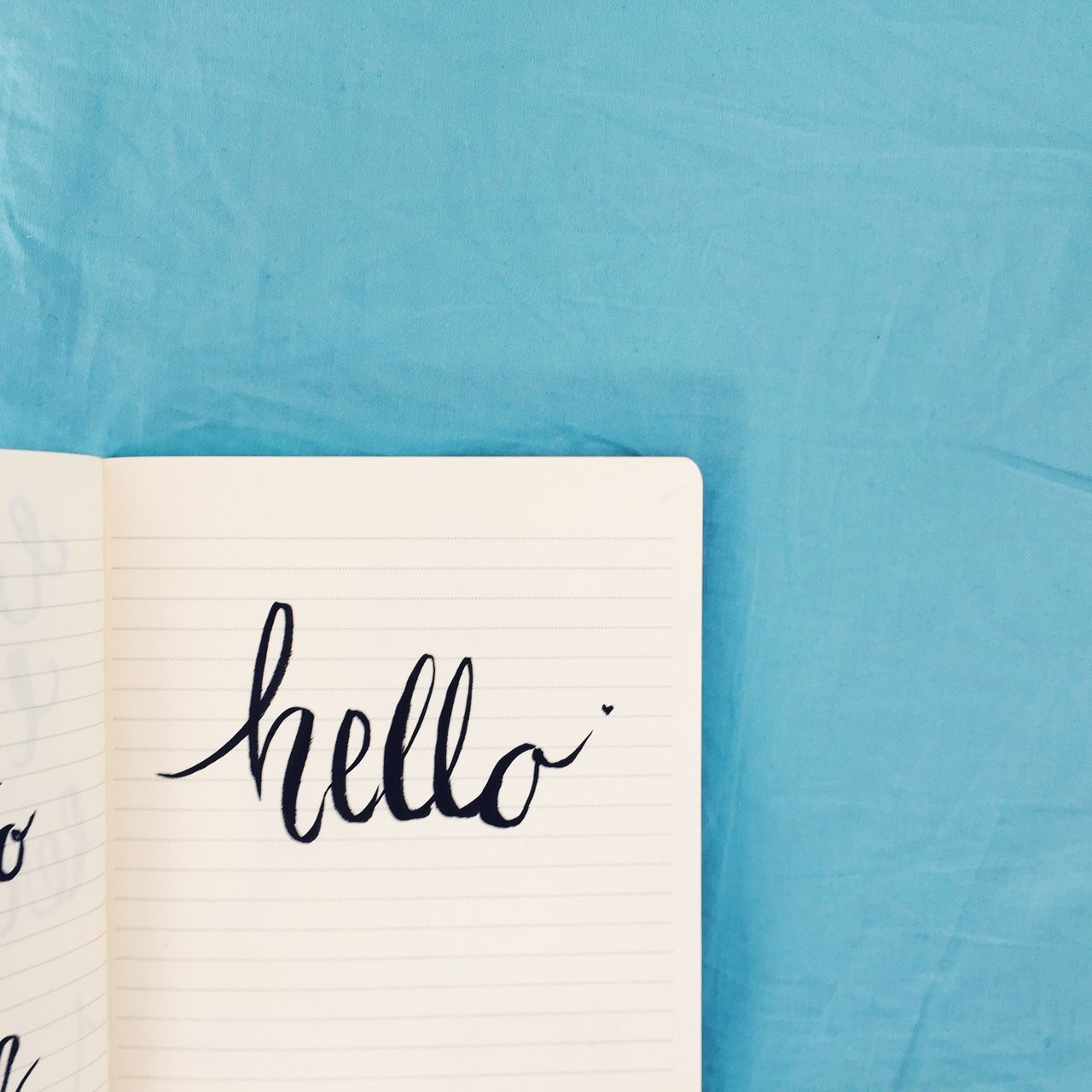 Hello written in brush lettering in a notebook Blue Brush Lettering Communication Day DIY Germany Handmade Hello IPhone IPhoneography Lettering Mobile Photography Munich München No People Notebook Paper Text Water Writing
