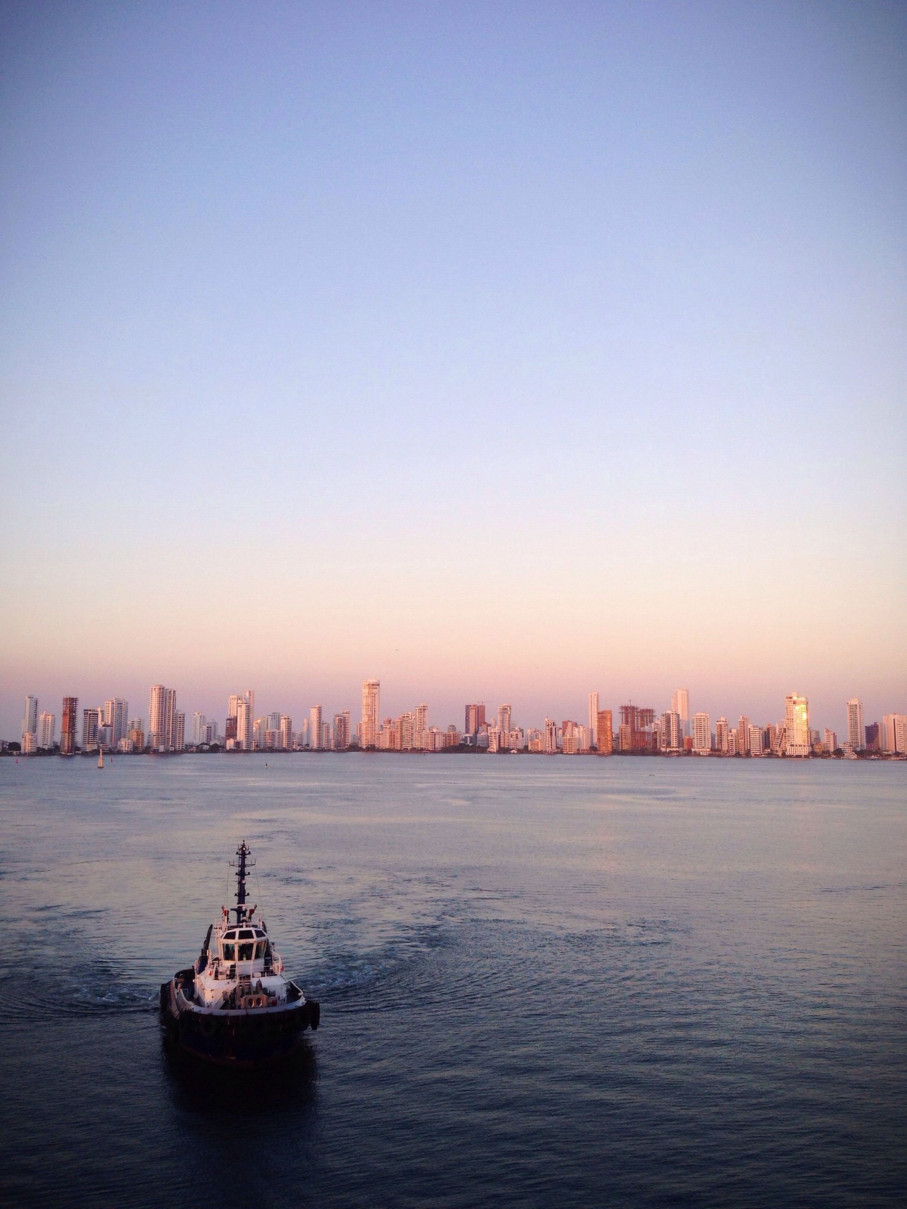 waterfront, water, nautical vessel, building exterior, architecture, sea, built structure, city, transportation, copy space, boat, cityscape, mode of transport, clear sky, river, urban skyline, sunset, harbor, skyscraper, sky