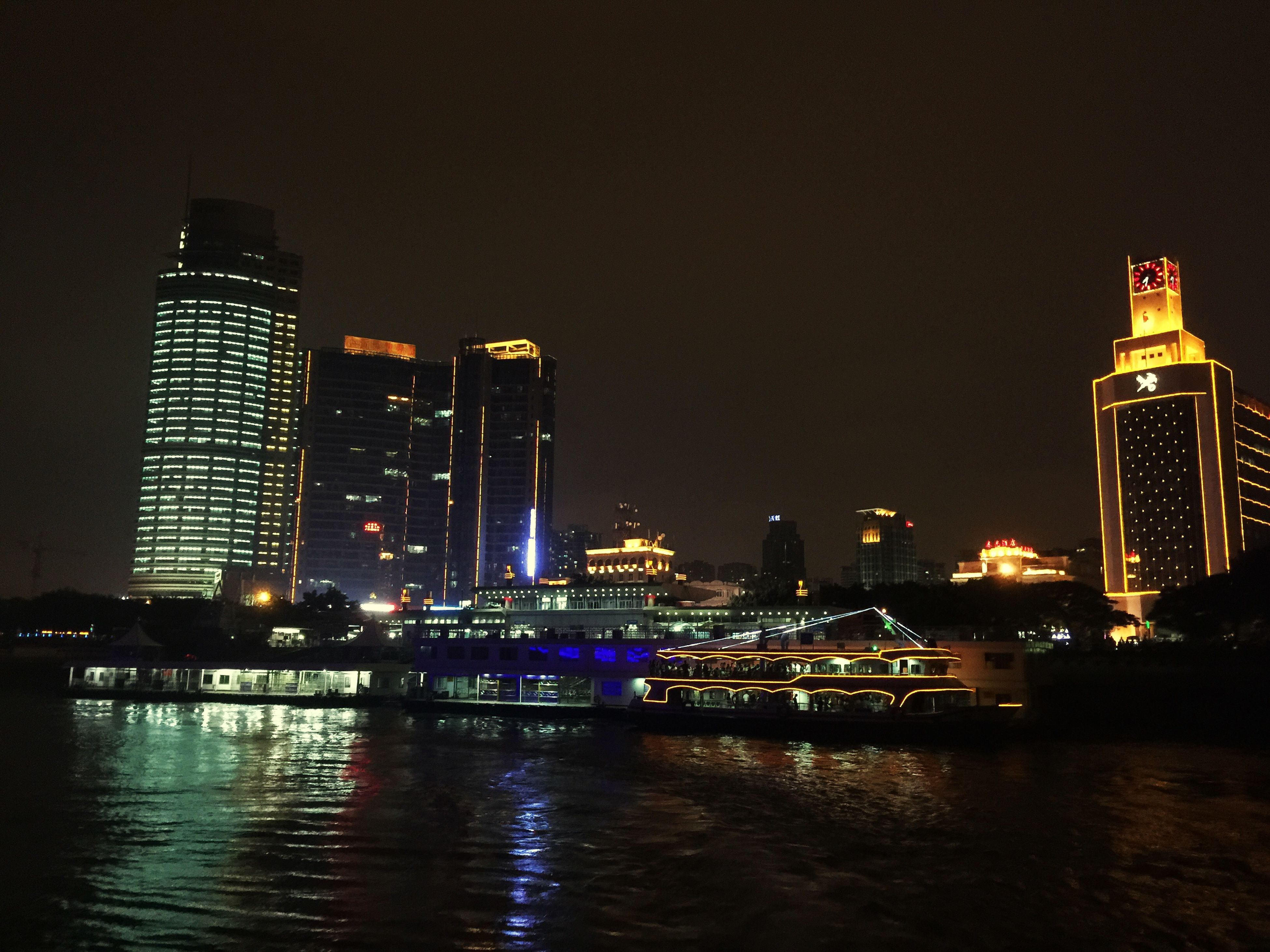 illuminated, building exterior, night, architecture, city, built structure, skyscraper, tower, waterfront, tall - high, modern, cityscape, office building, urban skyline, water, clear sky, river, reflection, financial district, copy space