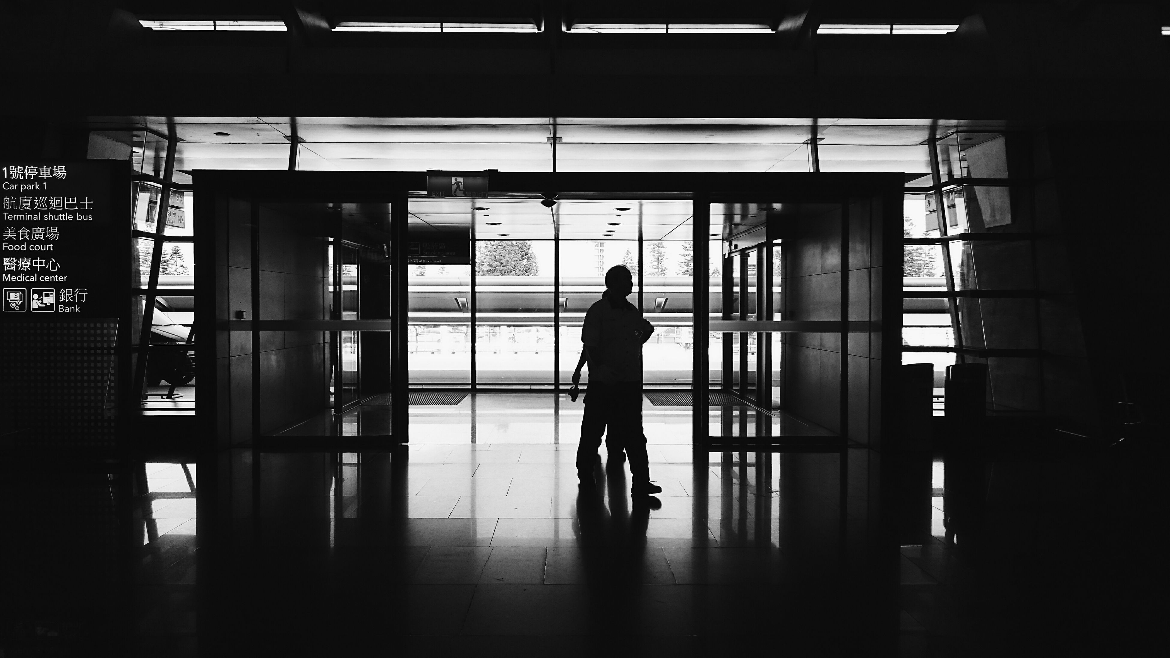 indoors, architecture, built structure, silhouette, lifestyles, men, full length, window, standing, walking, glass - material, leisure activity, person, reflection, rear view, building exterior, building, modern