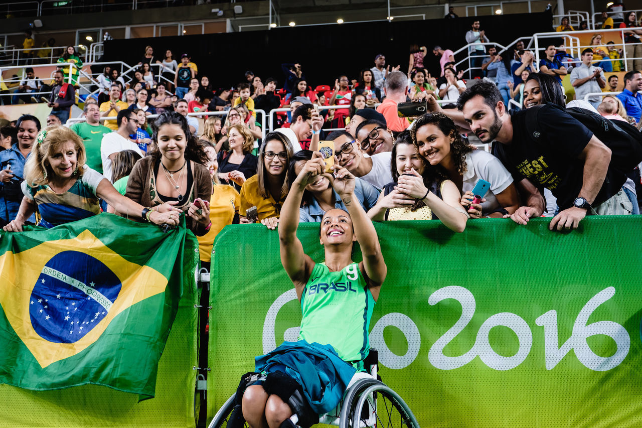 large group of people, stadium, crowd, sitting, fan - enthusiast, togetherness, men, happiness, spectator, leisure activity, outdoors, cheering, patriotism, excitement, women, audience, day, sport, cheerful, smiling, real people, encouragement, sports event, wheelchair, applauding, adult, young adult, people, adults only