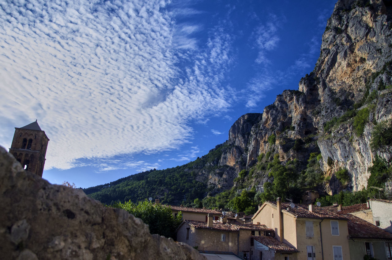 mountain, architecture, building exterior, rock - object, no people, built structure, sky, day, nature, scenics, low angle view, outdoors, mountain range, cloud - sky, beauty in nature