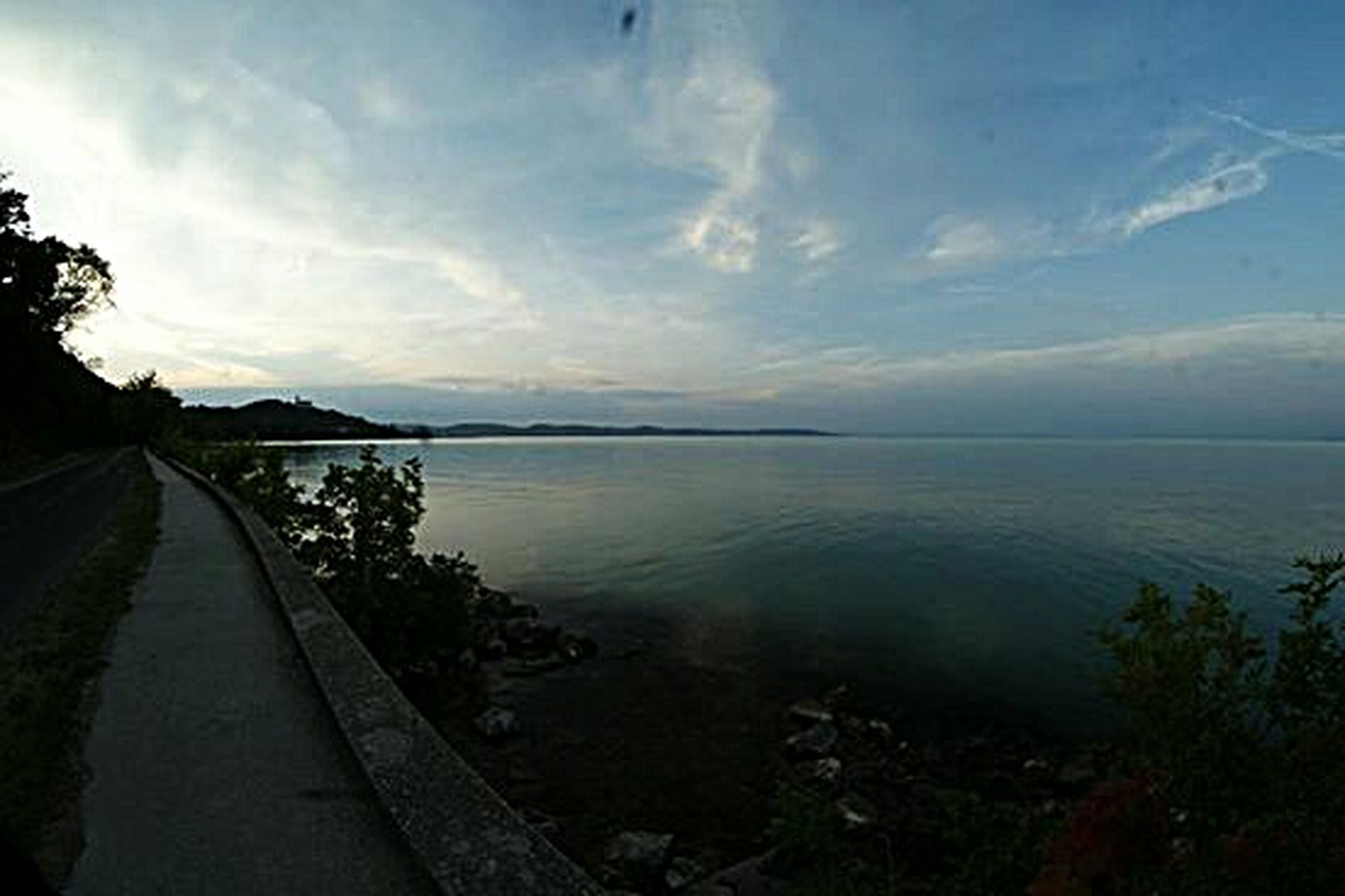 water, sky, tranquil scene, tranquility, scenics, beauty in nature, the way forward, cloud - sky, nature, sea, cloud, lake, tree, idyllic, horizon over water, panoramic, cloudy, plant, outdoors, non-urban scene