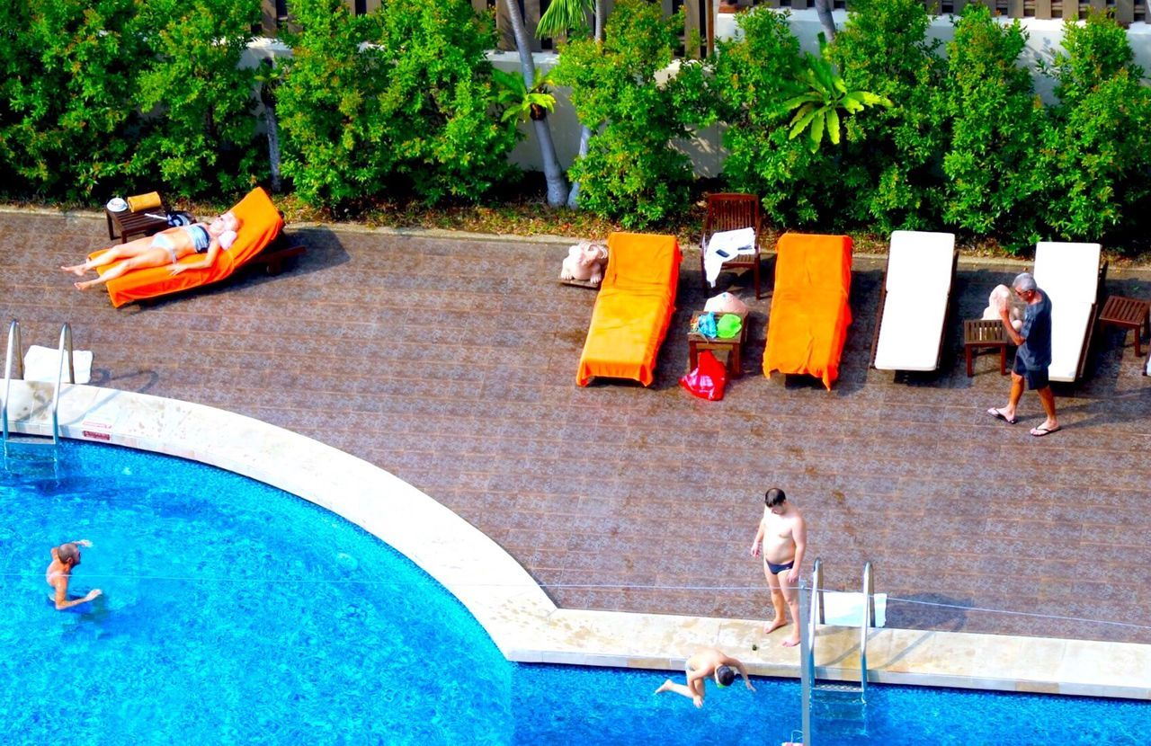High Angle View Of People At Poolside In Hotel