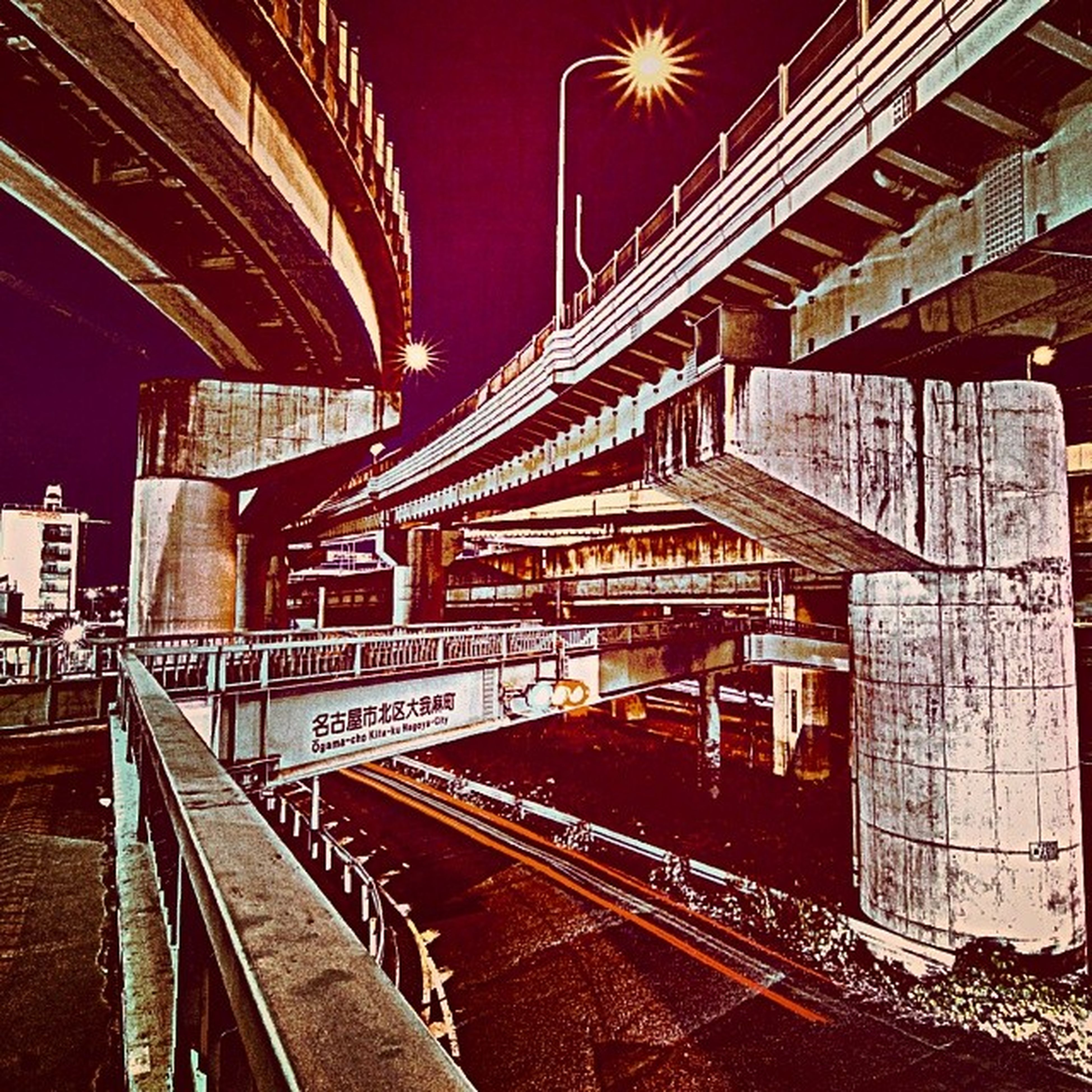 railroad track, illuminated, built structure, architecture, rail transportation, night, transportation, railroad station, the way forward, building exterior, public transportation, railroad station platform, diminishing perspective, lighting equipment, no people, connection, railing, outdoors, train - vehicle, long