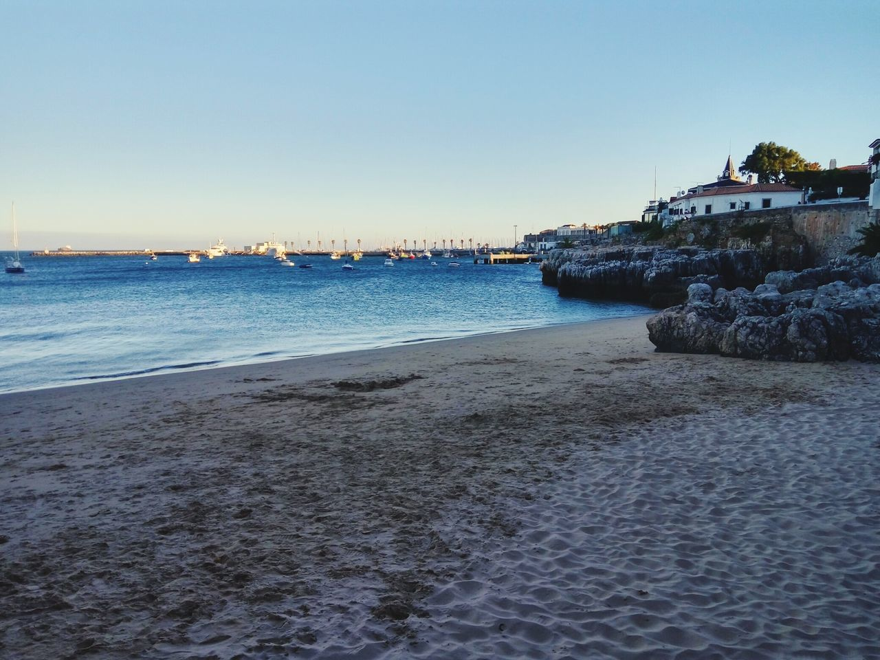 water, sea, beach, nature, sand, beauty in nature, outdoors, tranquility, scenics, no people, architecture, clear sky, tranquil scene, rock - object, sky, building exterior, built structure, travel destinations, sunset, city, day, nautical vessel