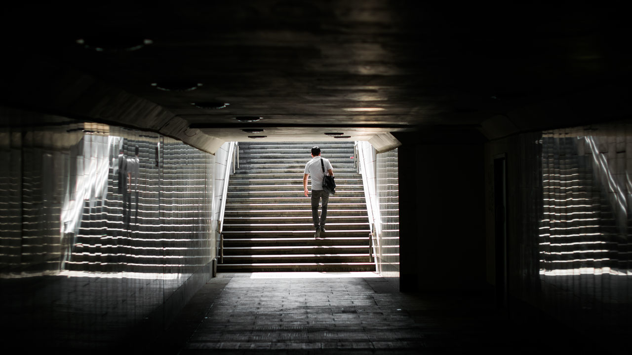 Rear View Of Man Climbing On Stairs At Underground Walkway
