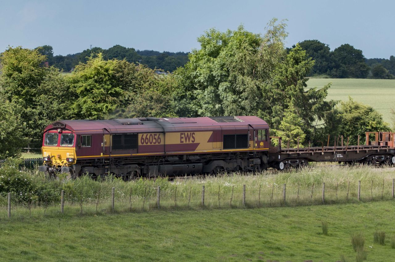 transportation, train - vehicle, mode of transport, tree, rail transportation, public transportation, day, land vehicle, field, railroad track, grass, green color, locomotive, outdoors, nature, no people, freight transportation, steam train, landscape, sky