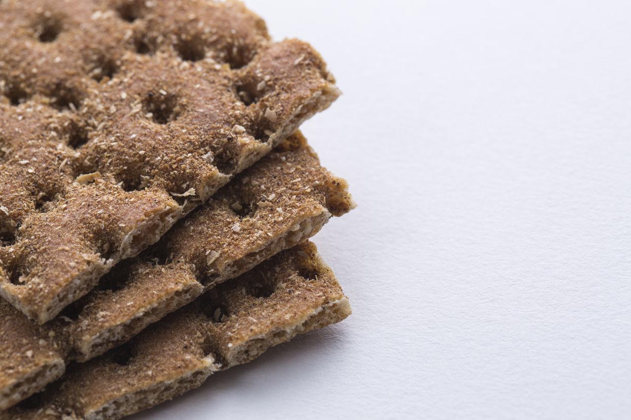Close up shot of the heap of crisp bread on white paper background. Bio Breakfast Close-up Copy Space Cracker Crisp Crispbread  Crunchy Food Healthy Food Heap Organic Rye Bread Stack Top View