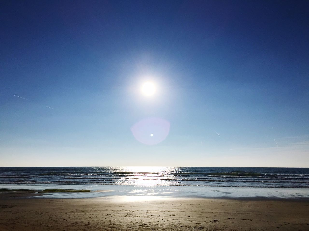 View Of Beach Against Clear Sky On Sunny Day